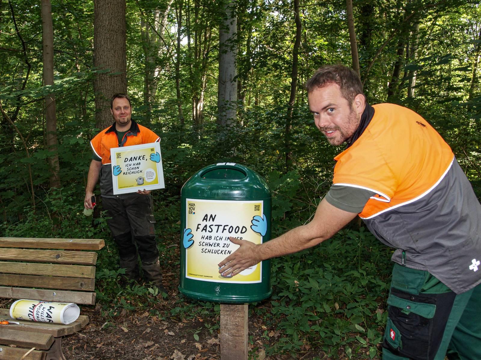 Zwei Männer, die einen Aufkleber an einem Mülleimer im Wald anbringen.