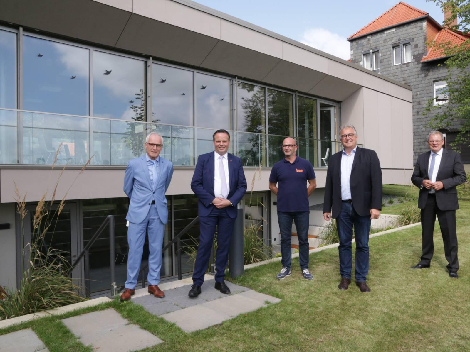 Vier Herren stehen vor einem neu gebauten Gebäude.