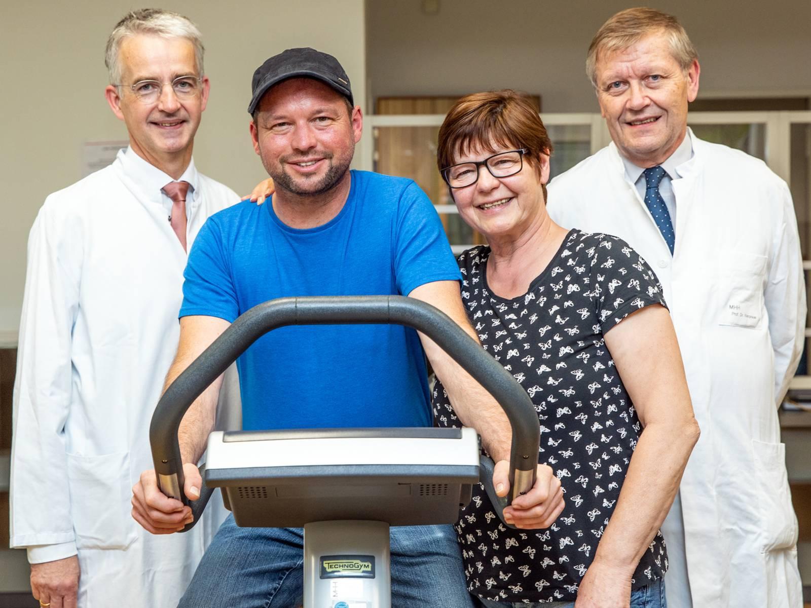 Mann auf einem Fitness-Fahrrad, daneben eine Frau und zwei Ärzte
