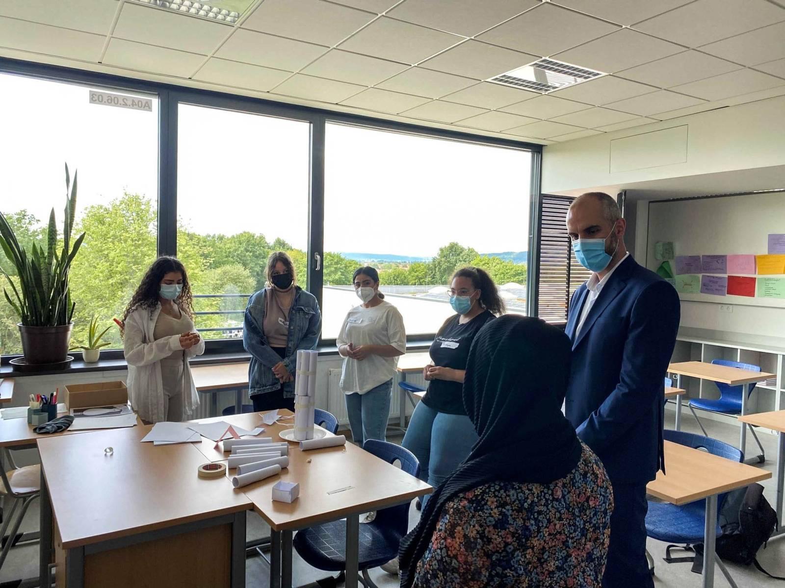 Oberbürgermeister Onay im Gespräch mit Schülerinnen im einem Klassenzimmer.