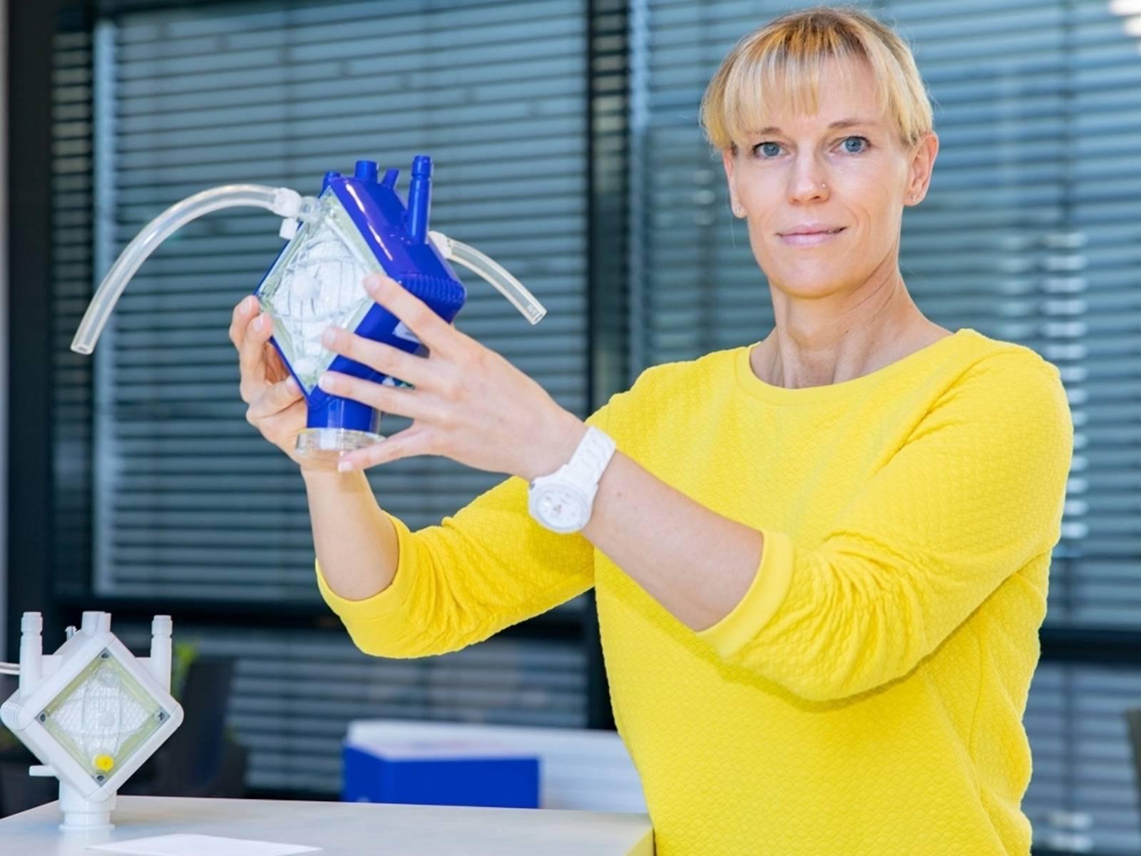 Eine Frau hält ein Gerät in den Händen.