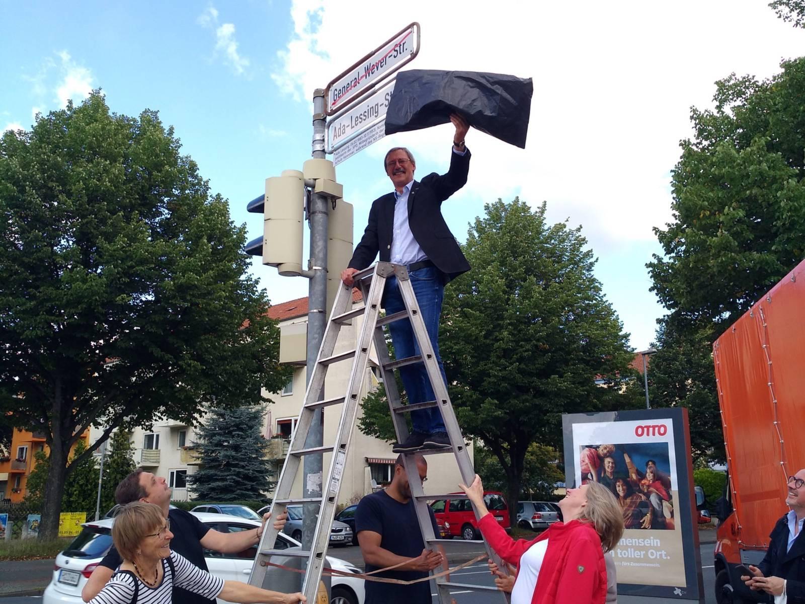 """Ein Mann auf einer Leiter enthüllt ein neues Straßenschild mit der Aufschrift """"Ada-Lessing-Straße"""""""