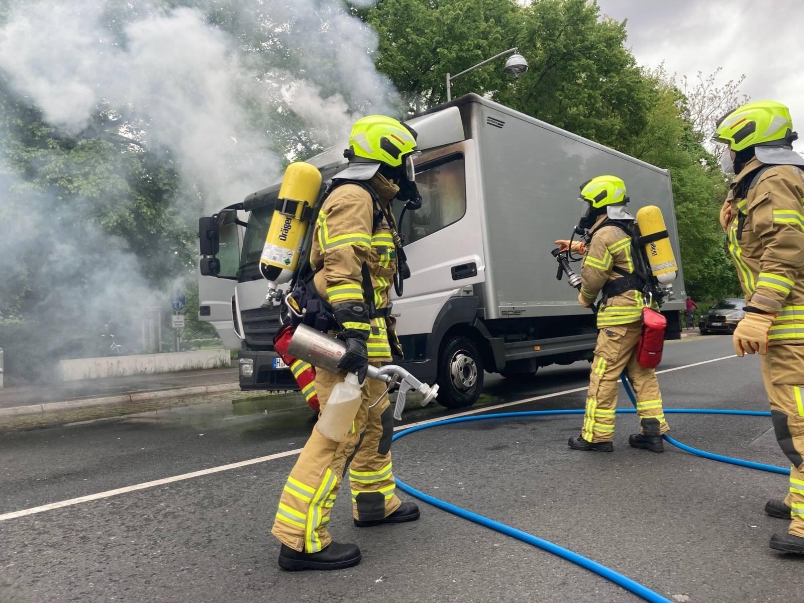 Feuerwehrleute löschen einen LKW.