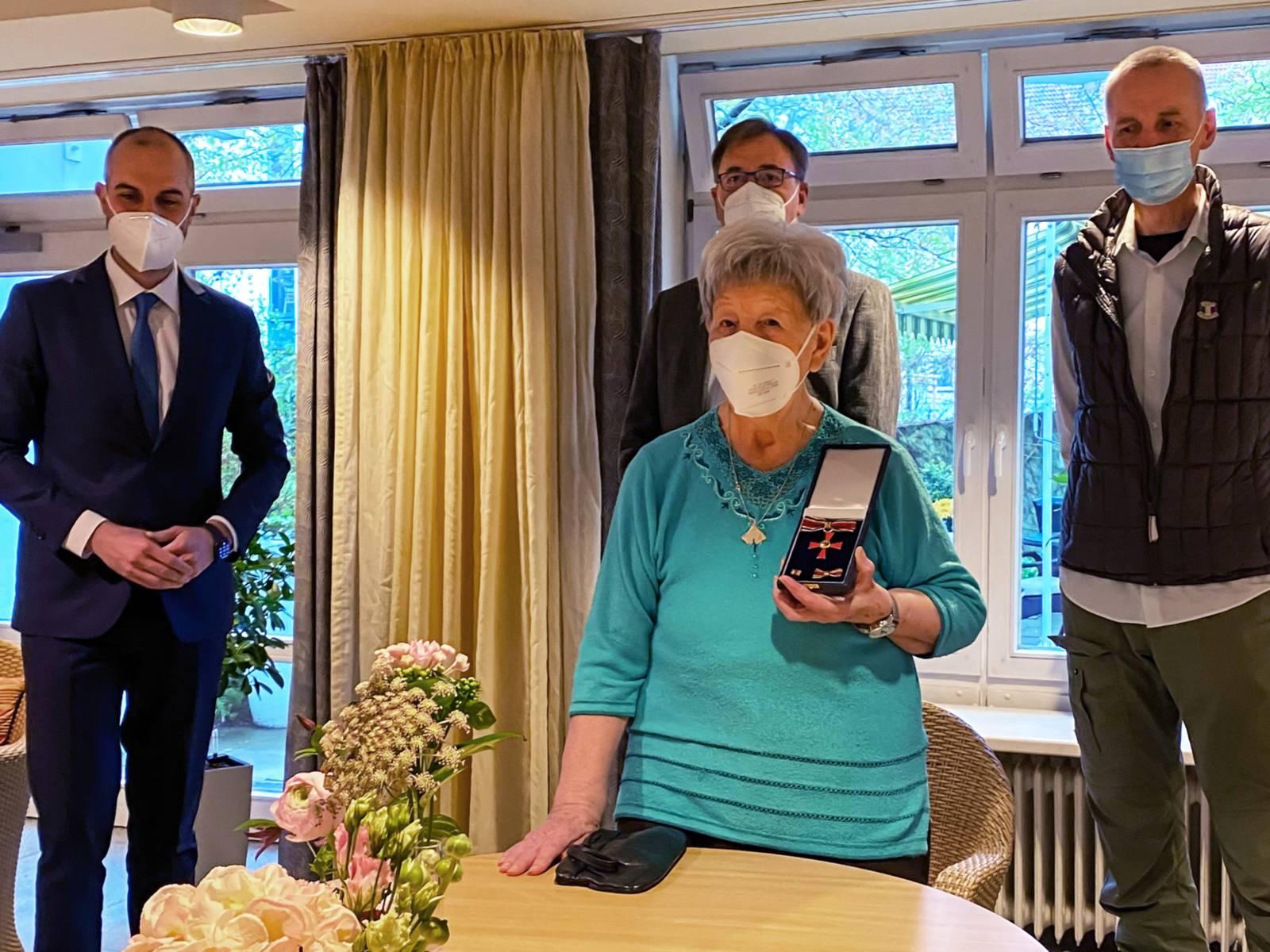 Vier Personen, Frau Ilse Schulz hält im Vordergrund einen Orden in den Händen, im Hintergrund stehen der Oberbürgermeister sowie die Söhne von Frau Schulz