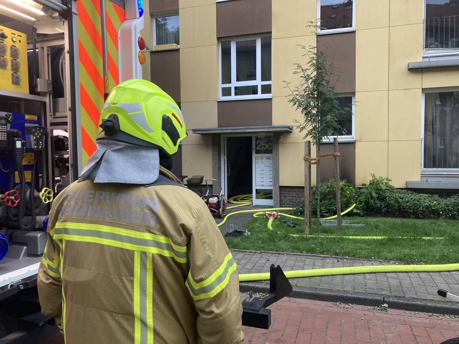 Eine Feuerwehrkraft steht vor einem Haus