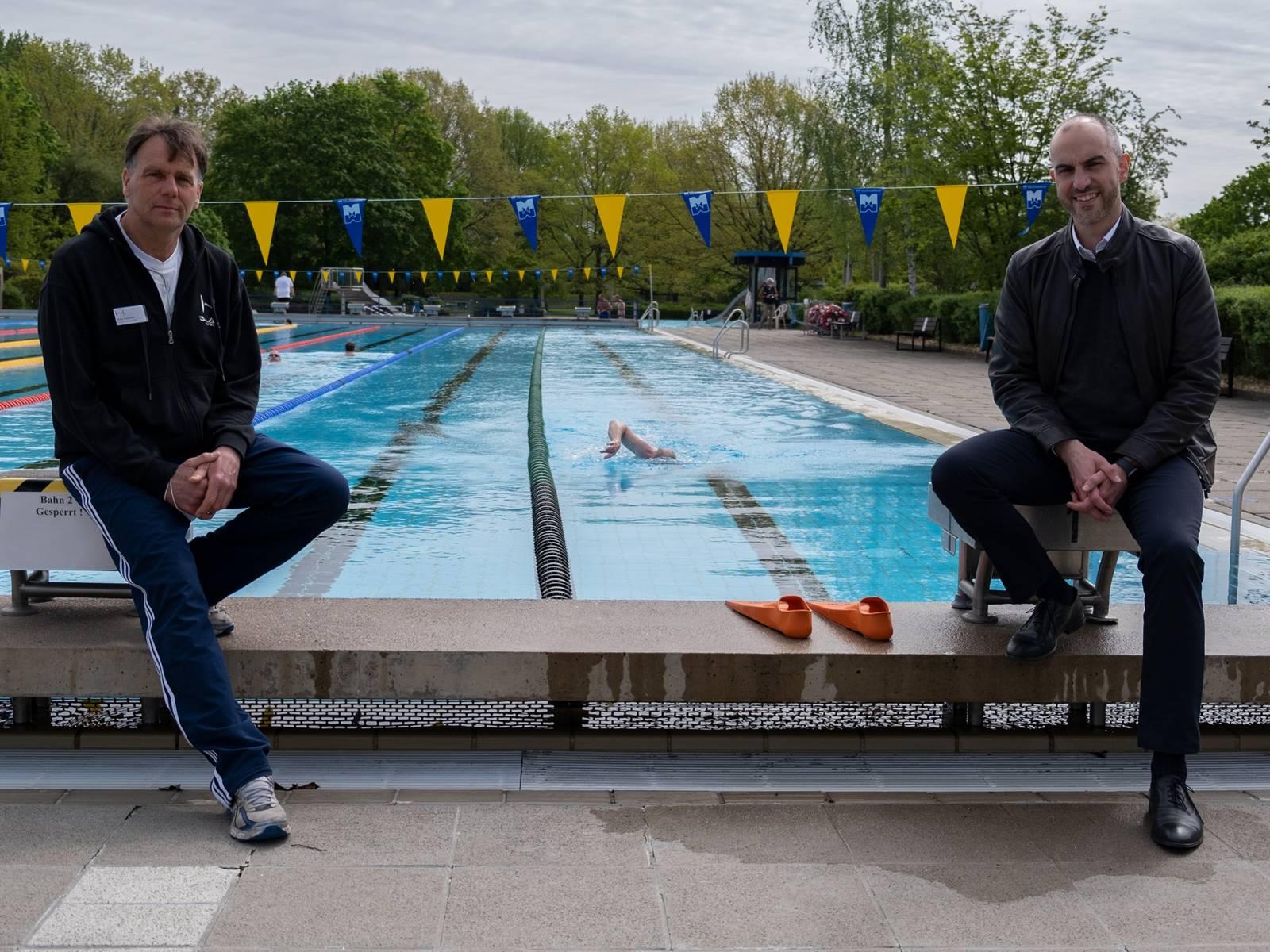 Zwei Männer sitzen am Rand eines Schwimmbeckens