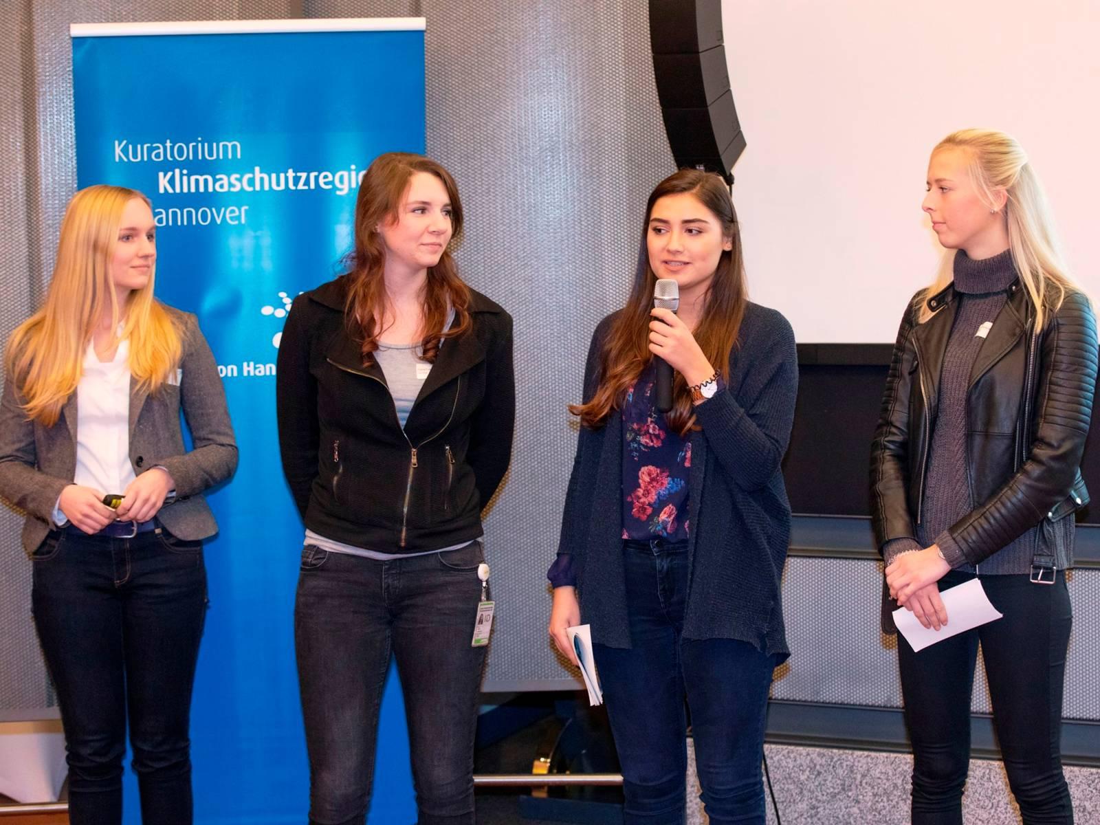 Vier junge Frauen. Eine spricht in ein Mikrofon.