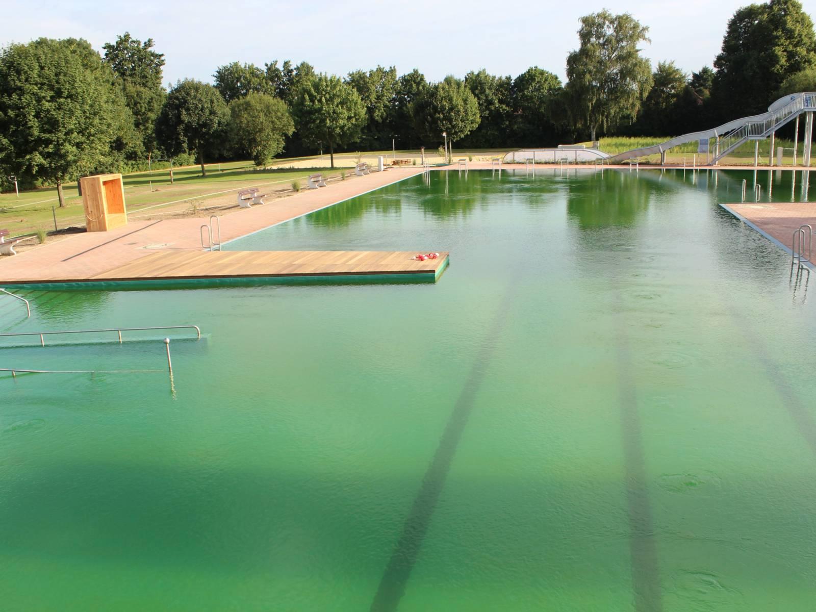 Ein Schwimmbecken, im Hintergrund eine Rutsche mit grünlich schimmerndem Wasser. Auf dem Grund erkennt man die Markierung für die Schwimmbahnen.