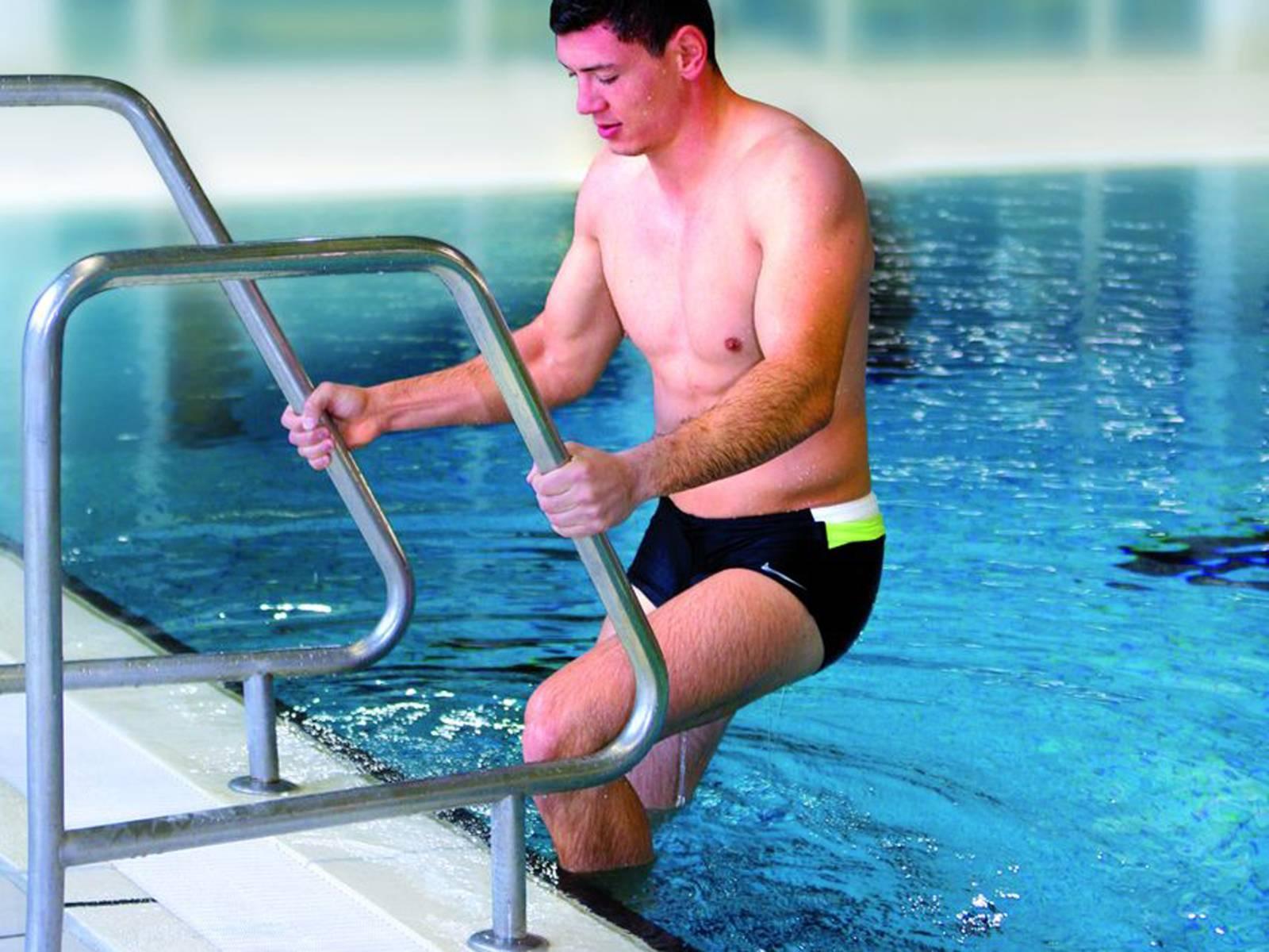 Ein junger Mann geht über eine Badeleiter in das Schwimmbecken eines Hallenbades