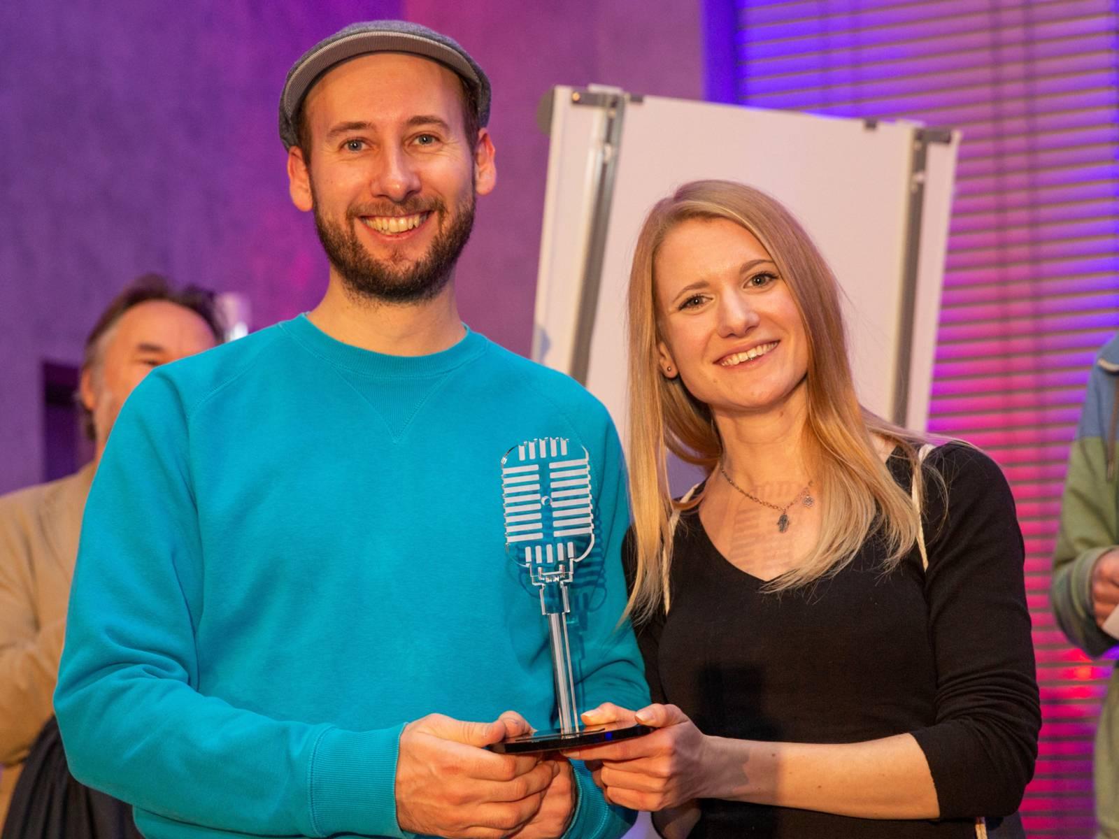Ein Mann und eine Frau, beide halten einen gläsernen Pokal in Form eines Mikrofons in den Händen
