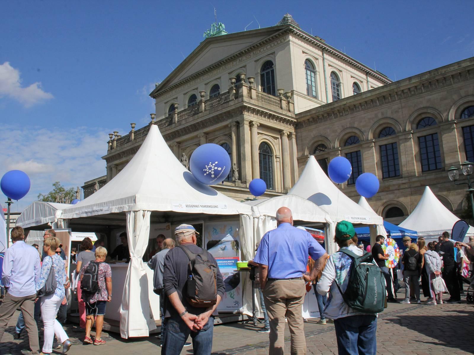 Eine Veranstaltung mit vielen weißen Pavillons auf einem Platz vor einem alten Gebäude: der Oper in Hannover.