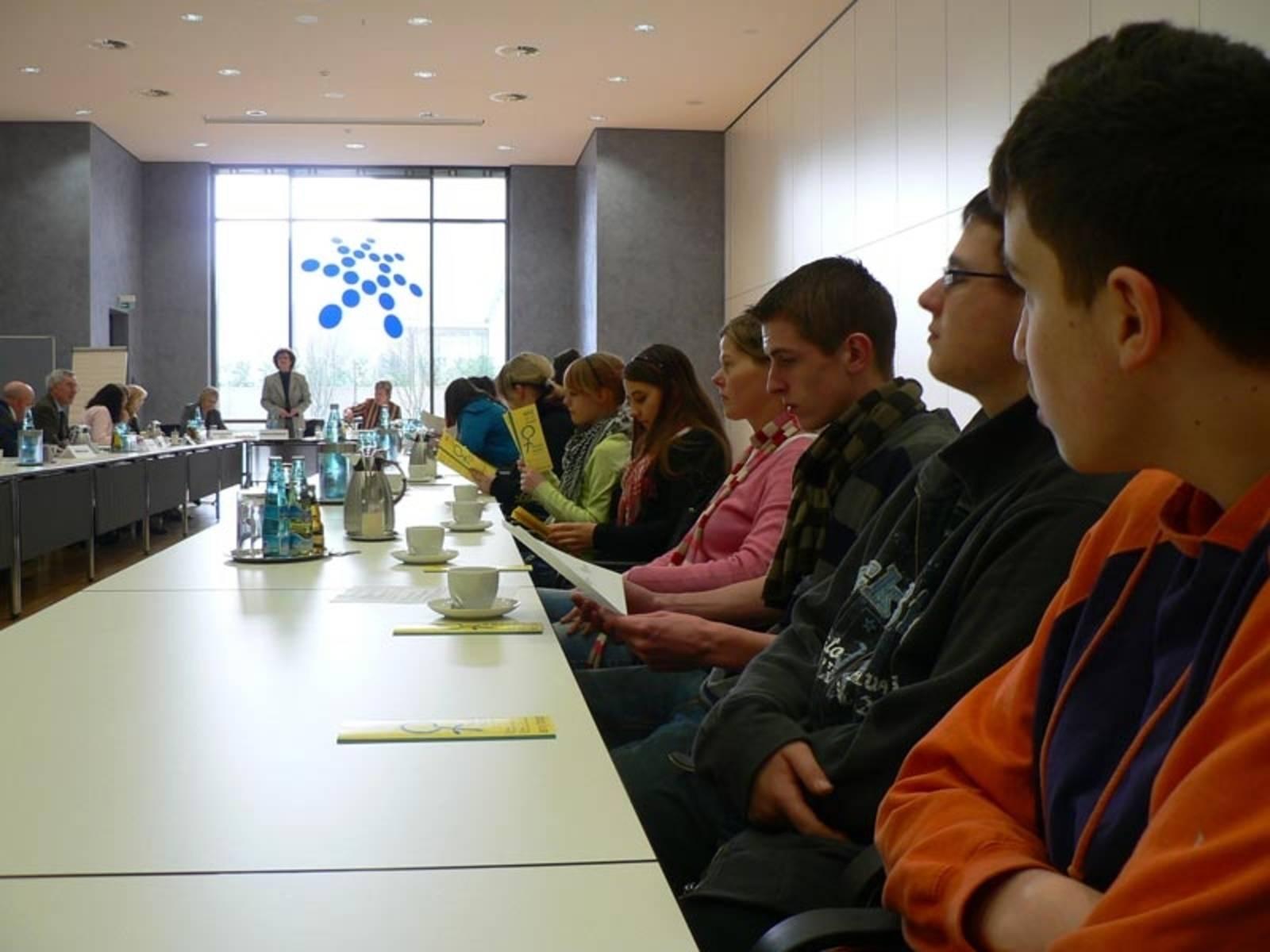 Schülerinnen und Schüler am einm langen Konferenztisch an dessen Ende eine Frau steht