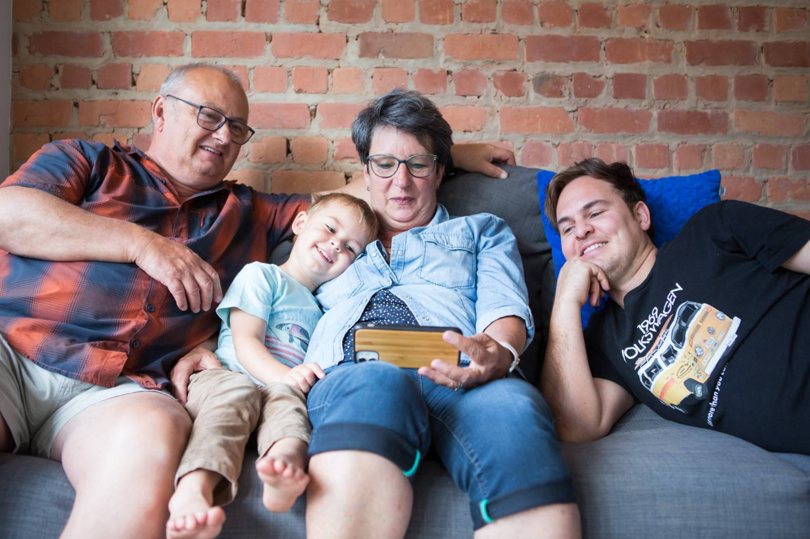 Grandparents watching a video on a smartphone with their grandson