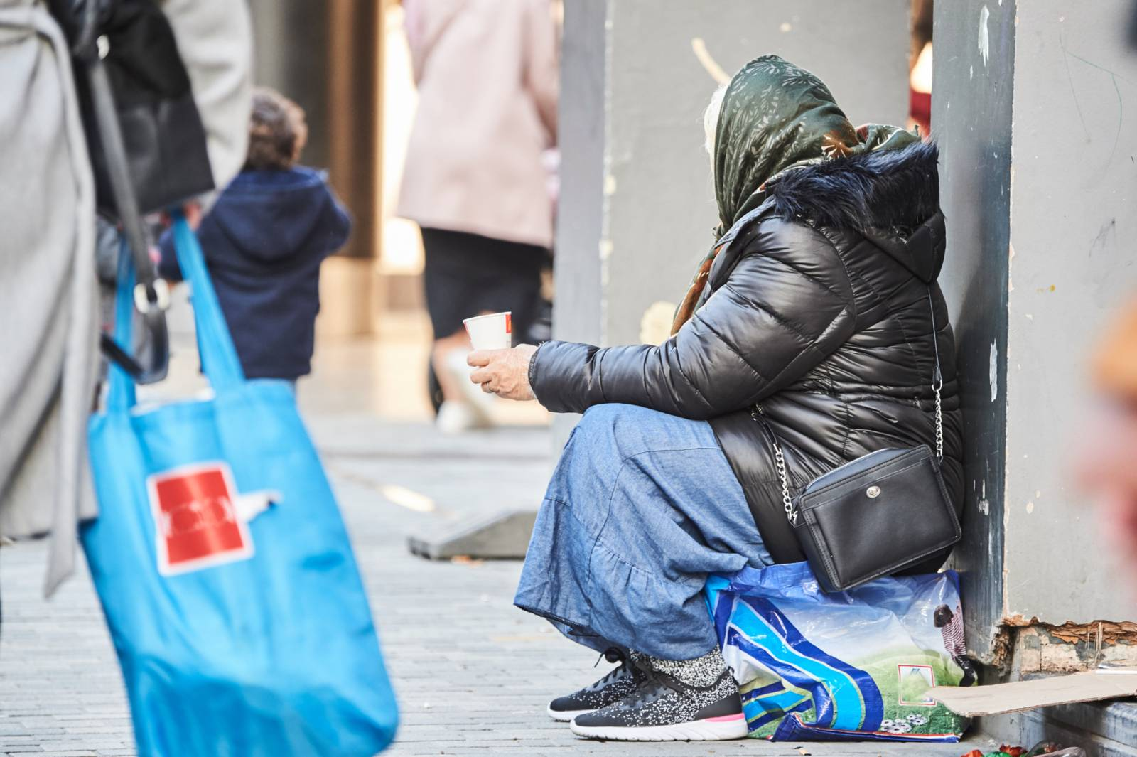 Homeless person begging on a busy shopping street