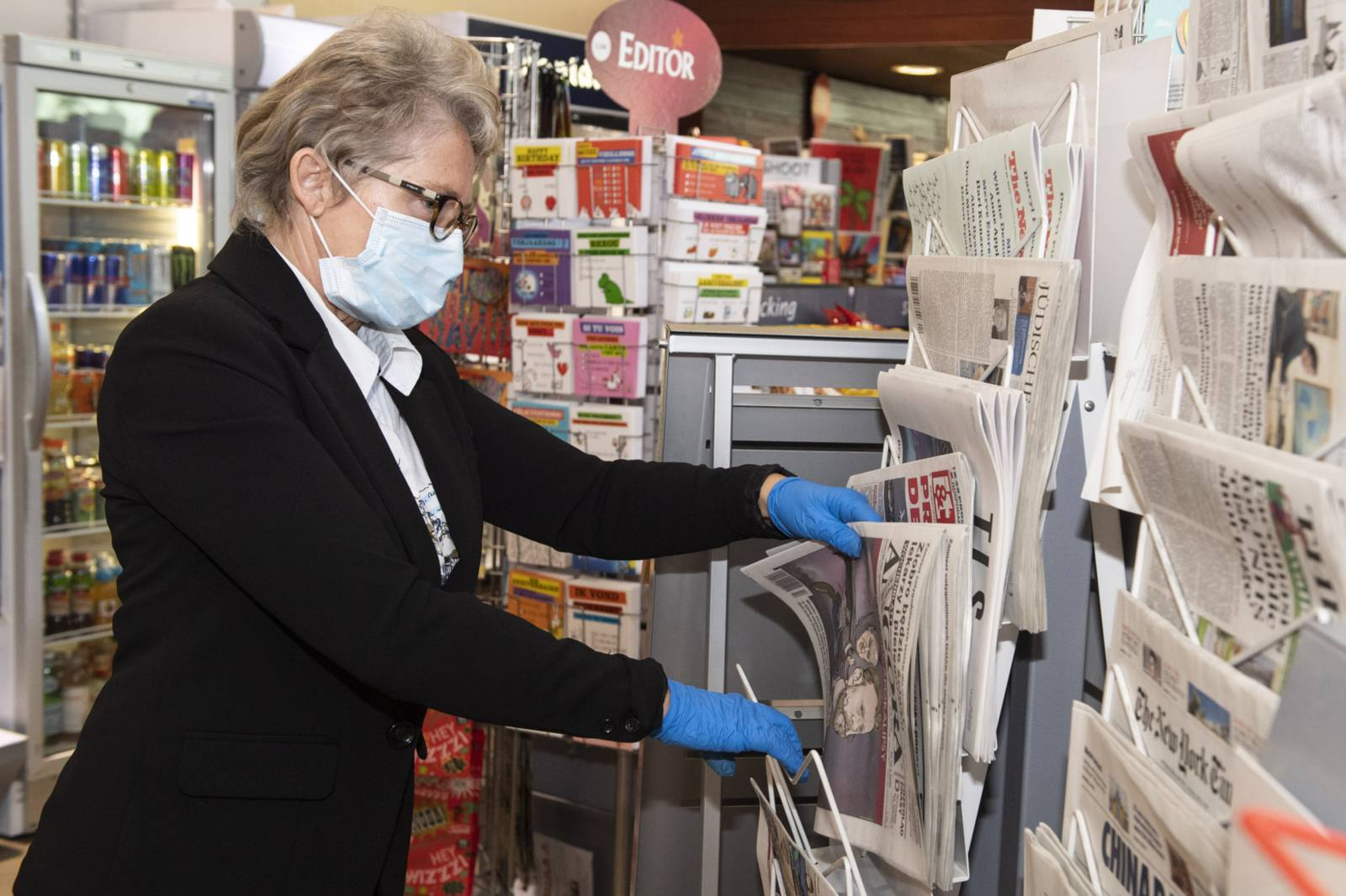 A newspaper seller wearing a protective mask and gloves during the coronavirus pandemic in Brussels