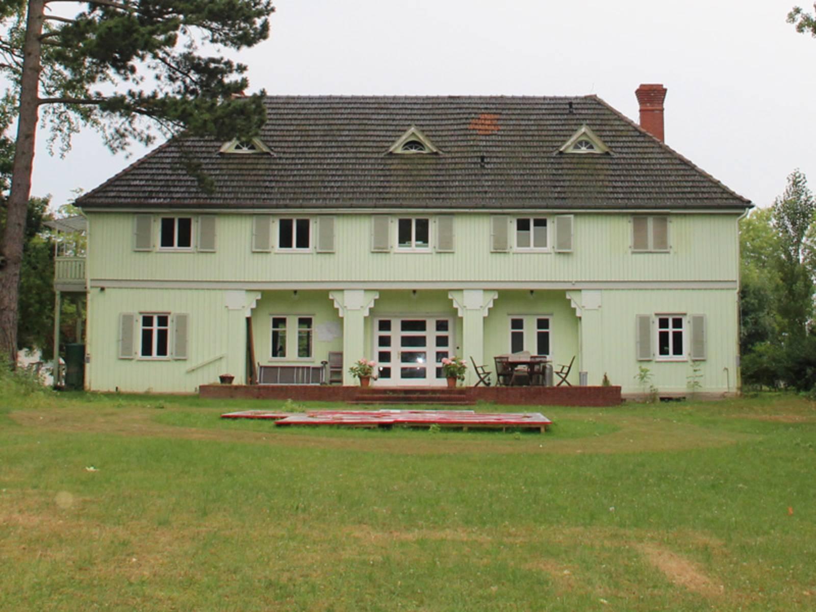 Älteres,  grünes Gebäude mit großer Rasenfläche im Vordergrund