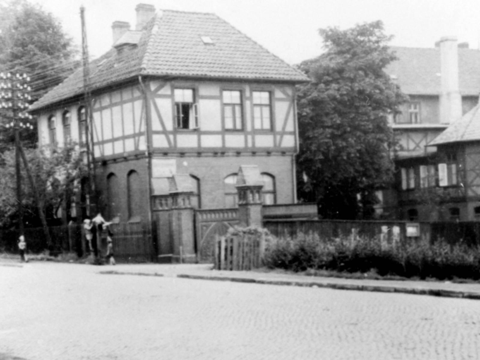 Schwarz-Weiß-Foto: Hinter einem gemauerten Eingangstor steht ein Ensemble mehrerer mehrgeschossiger Fachwerkhäuser.