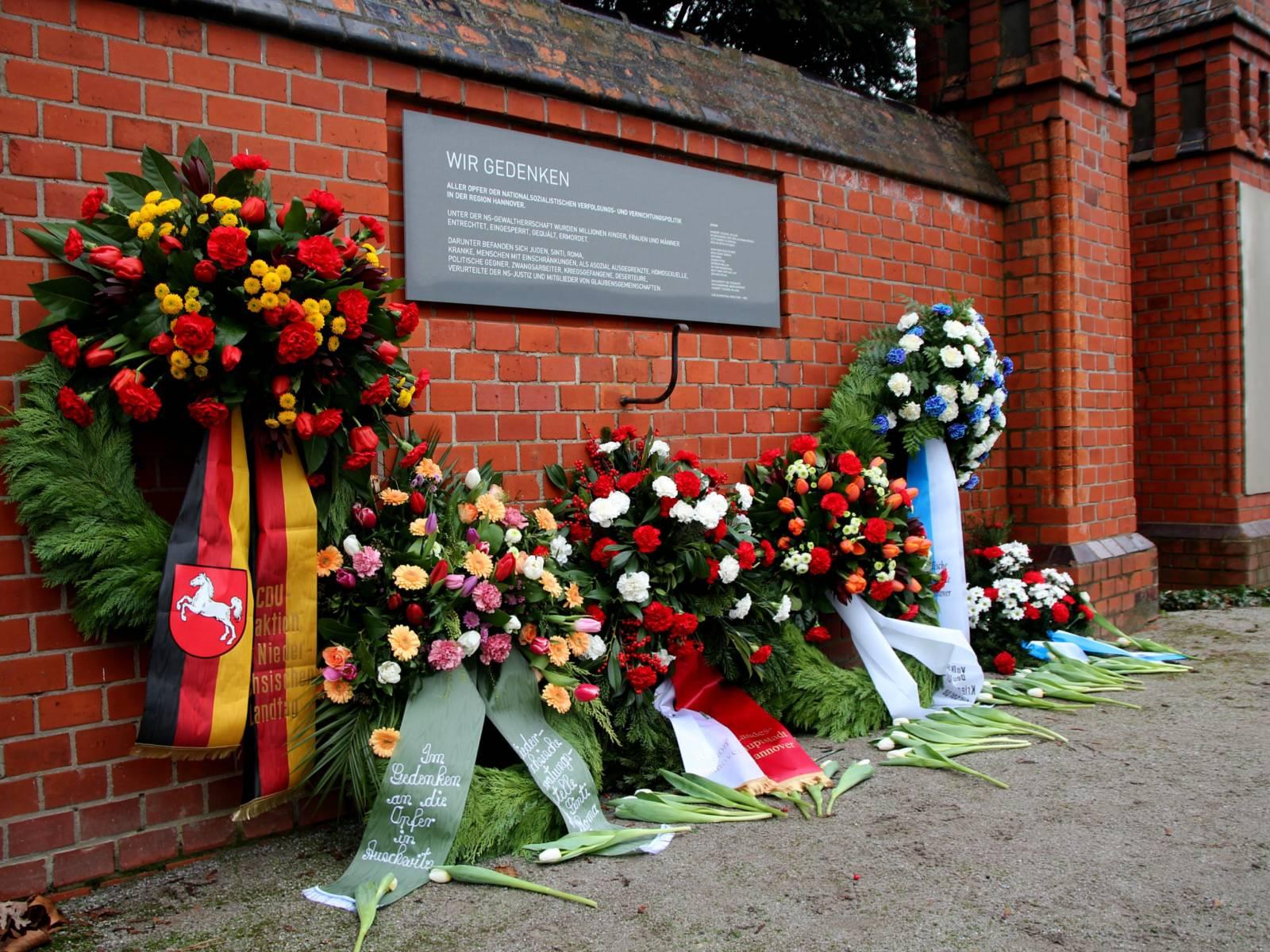 Sechs Blumenkränze abgelegt vor einer Gedenkwand.