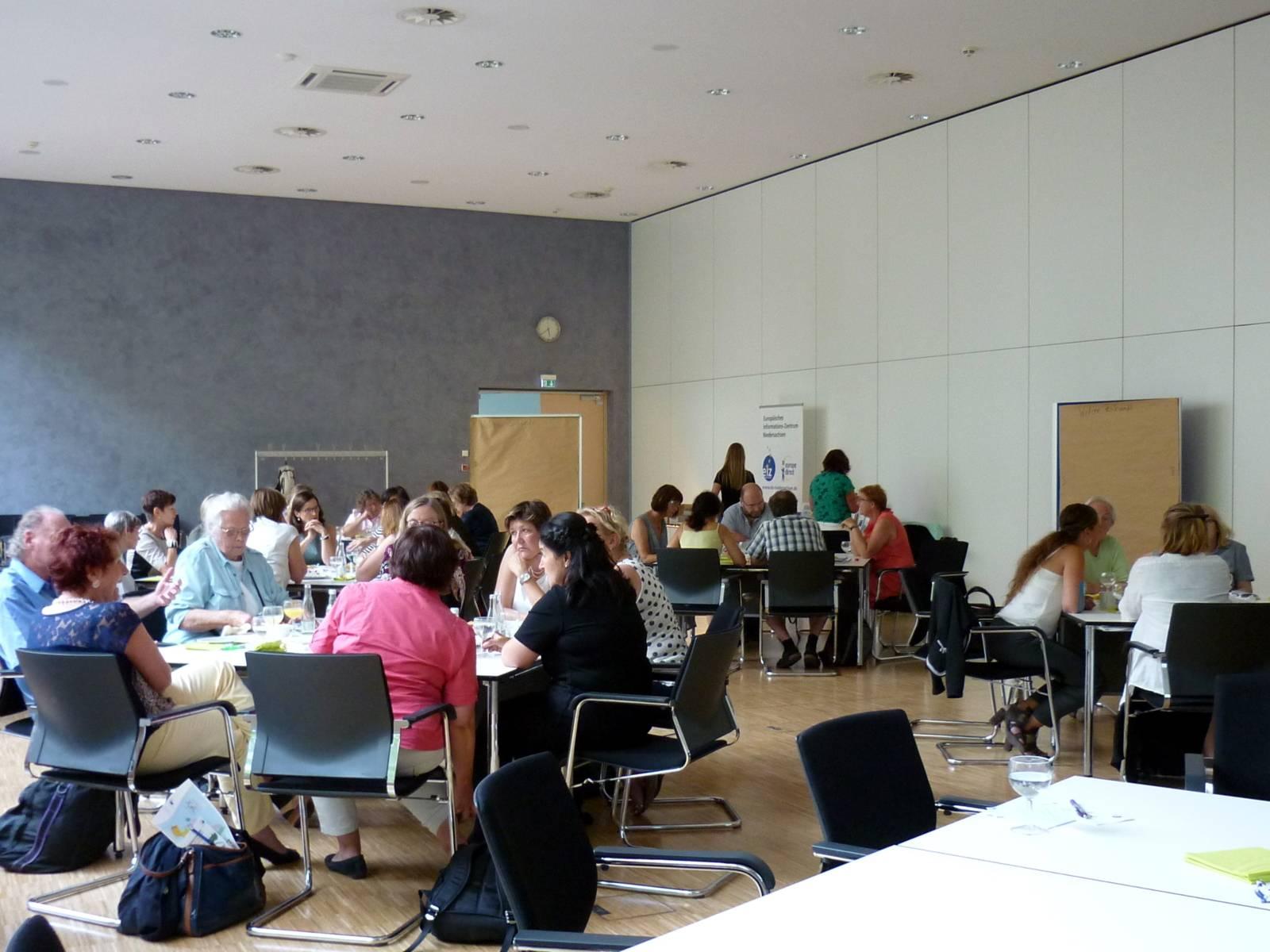 Sitzungsraum mit vielen Menschen die an Gruppentischen sitzen.