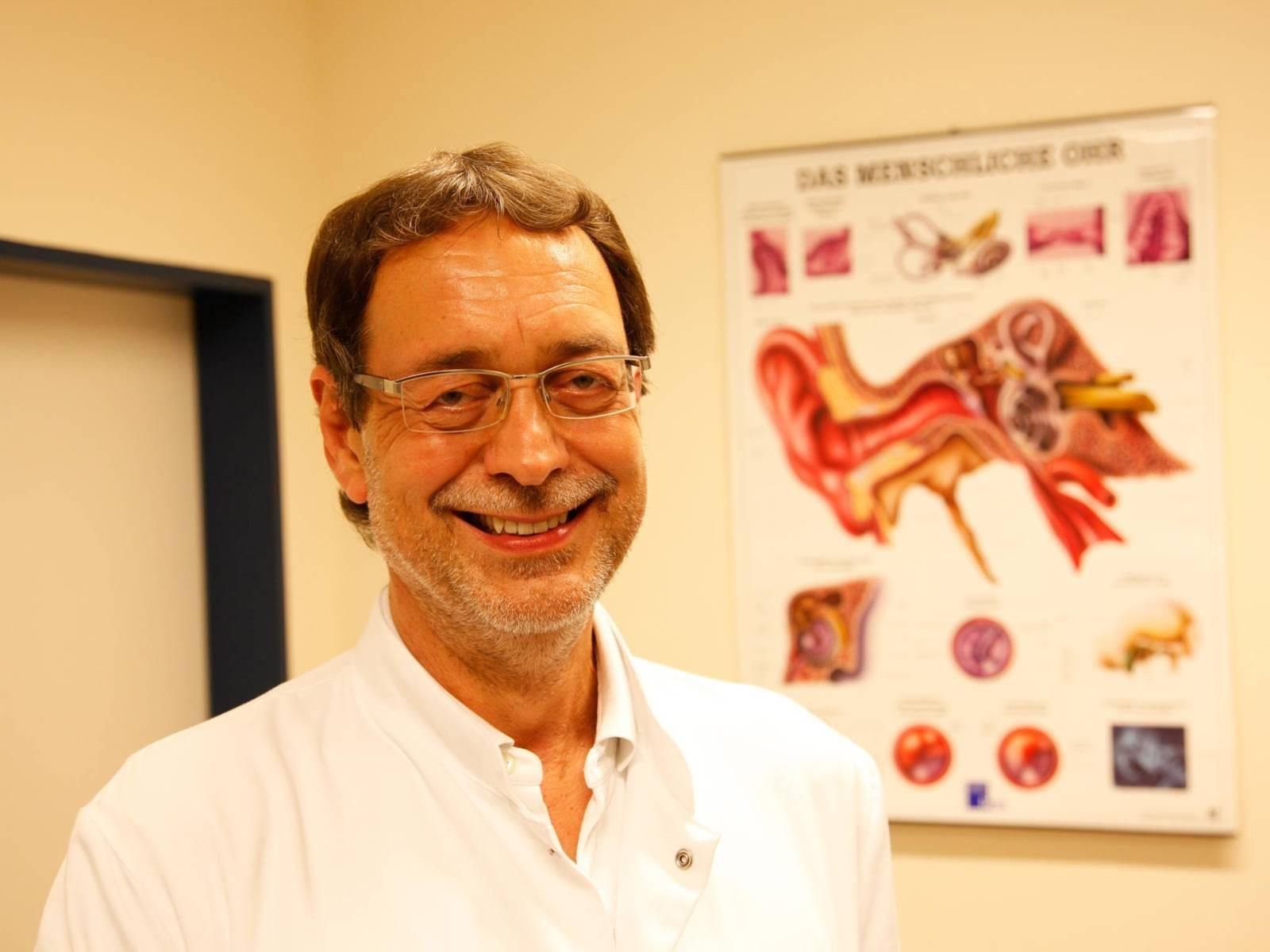 Ein Mann in einem weißen Kittel und mit Brille steht in einem Raum. An der Wand hängt eine Lehrtafel zum menschlichen Ohr.