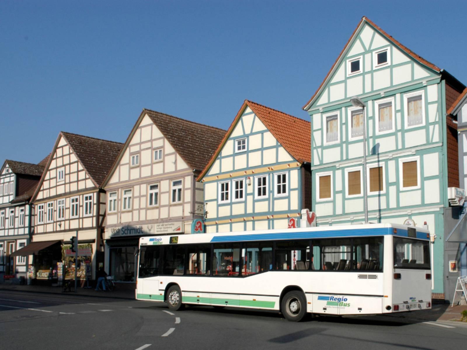 Ein Bus der RegioBus biegt um eine Kurve auf die Marktstraße in Burgdorf ein, im Hintergrund steht eine Reihe alter Fachwerkhäuser dicht an dicht nebeneinander.