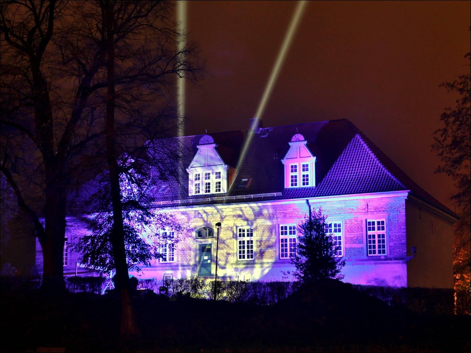 Foto vom Schlossleuchten 2012: Schloss Landestrost leuchtet in blauem Licht, zwei starke Scheinwerfer malen außerdem zwei Lichtsäulen in den Himmel.