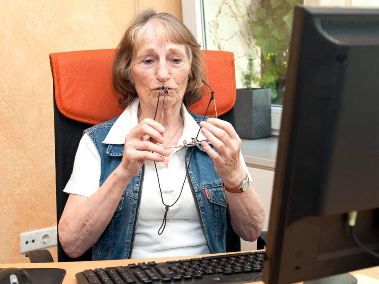 Eine ältere Frau an einem Schreibtisch. Sie hat die Bügel ihrer Brille an ihrem Mund und wirkt nachdenklich.