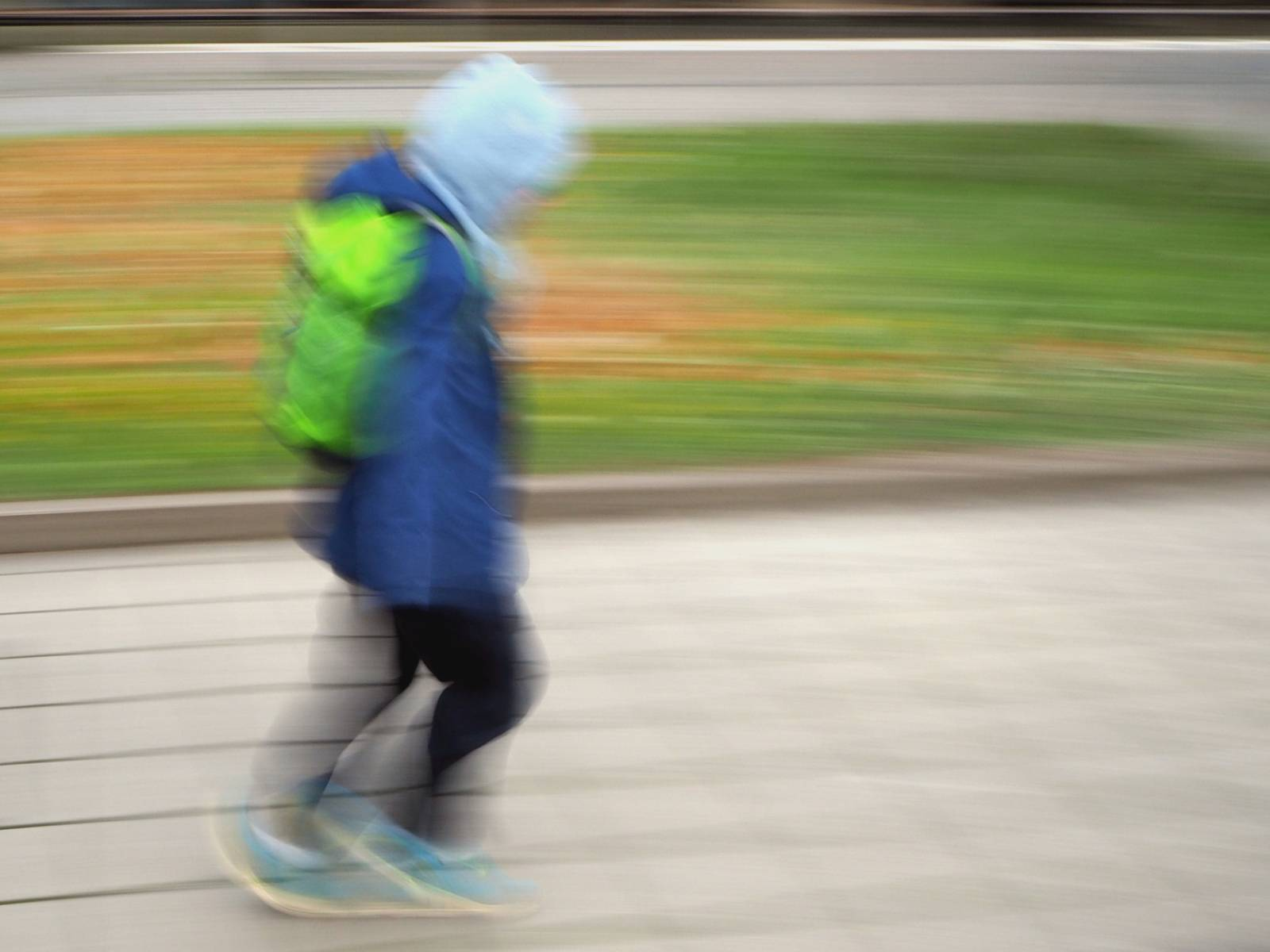 Ein Kind läuft schnell über einen gepflasterten Weg.