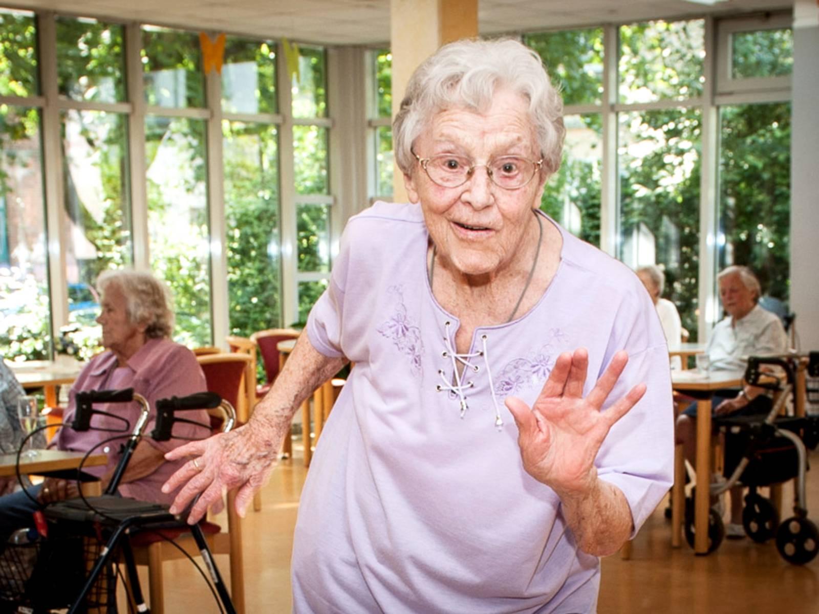 Eine ältere Dame macht einen Sprung nach vorne.