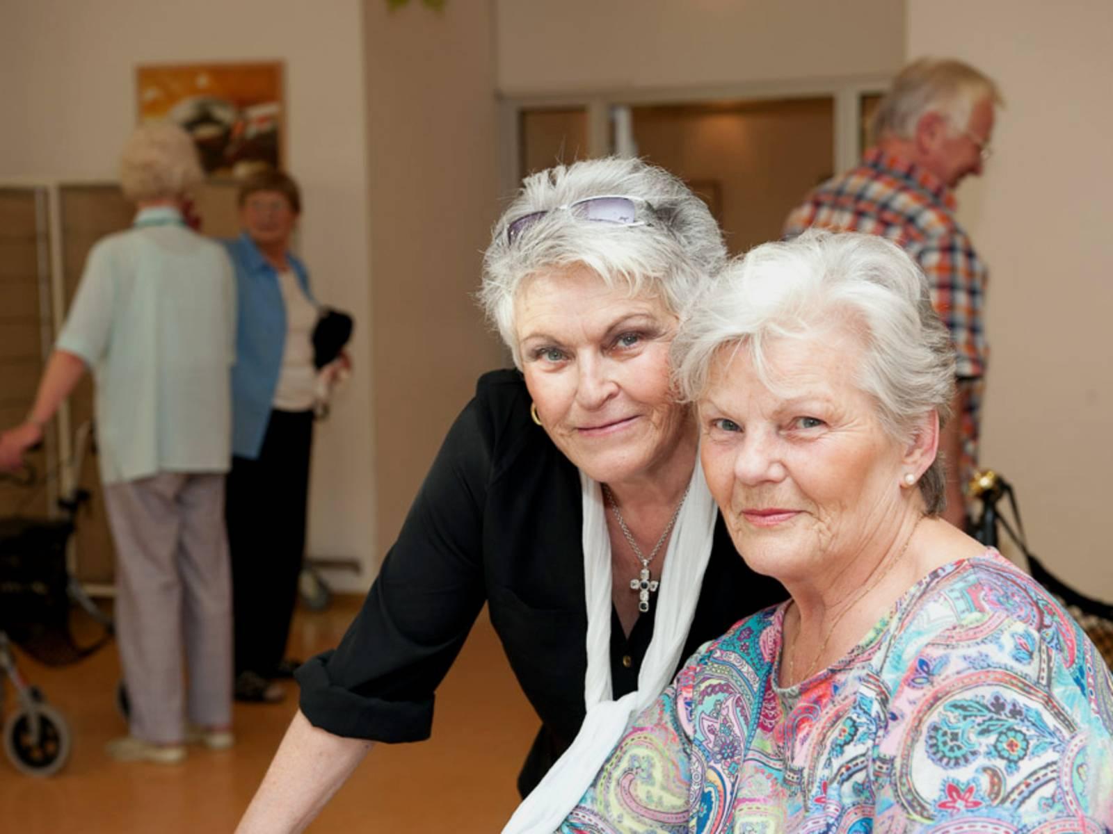 Zwei ältere Frauen halten ihre Köpfe nebeneinander und blicken in die Kamera.