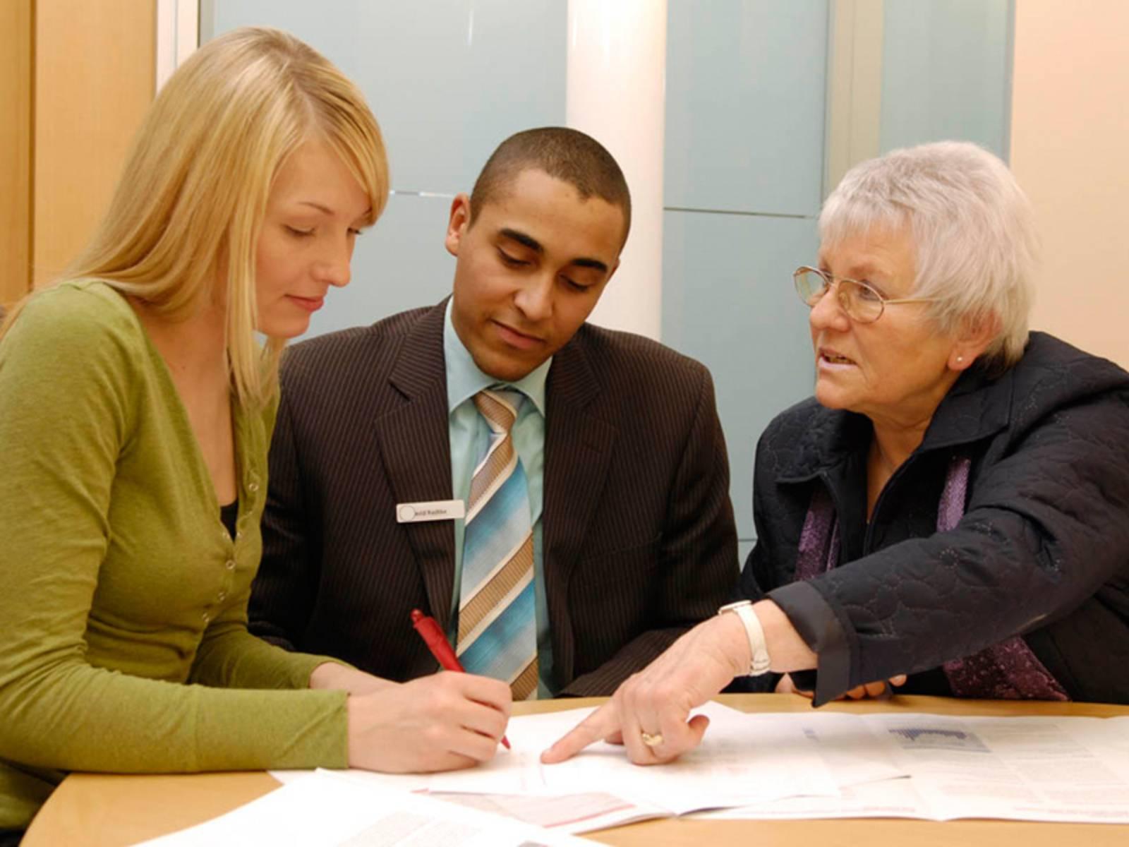 Eine junge Frau, ein junger Mann und eine ältere Frau an einem Tisch im Gespräch. Vor ihnen liegen ausgebreitet Unterlagen. Die ältere Frau zeigt auf eines der Papiere und die jüngere Frau macht Notizen.