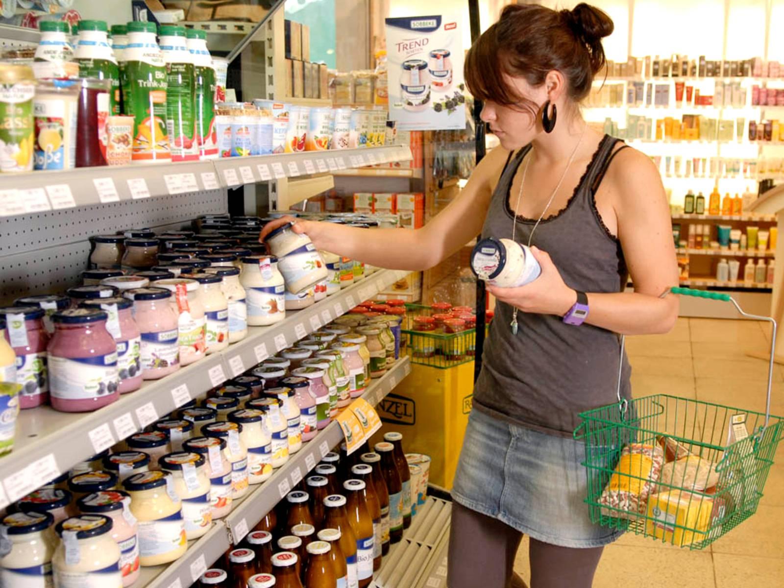 Eine junge Frau am Kühlregal eines Supermarktes und vergleicht Milchprodukte, am linken Arm trägt sie einen Einkaufskorb.