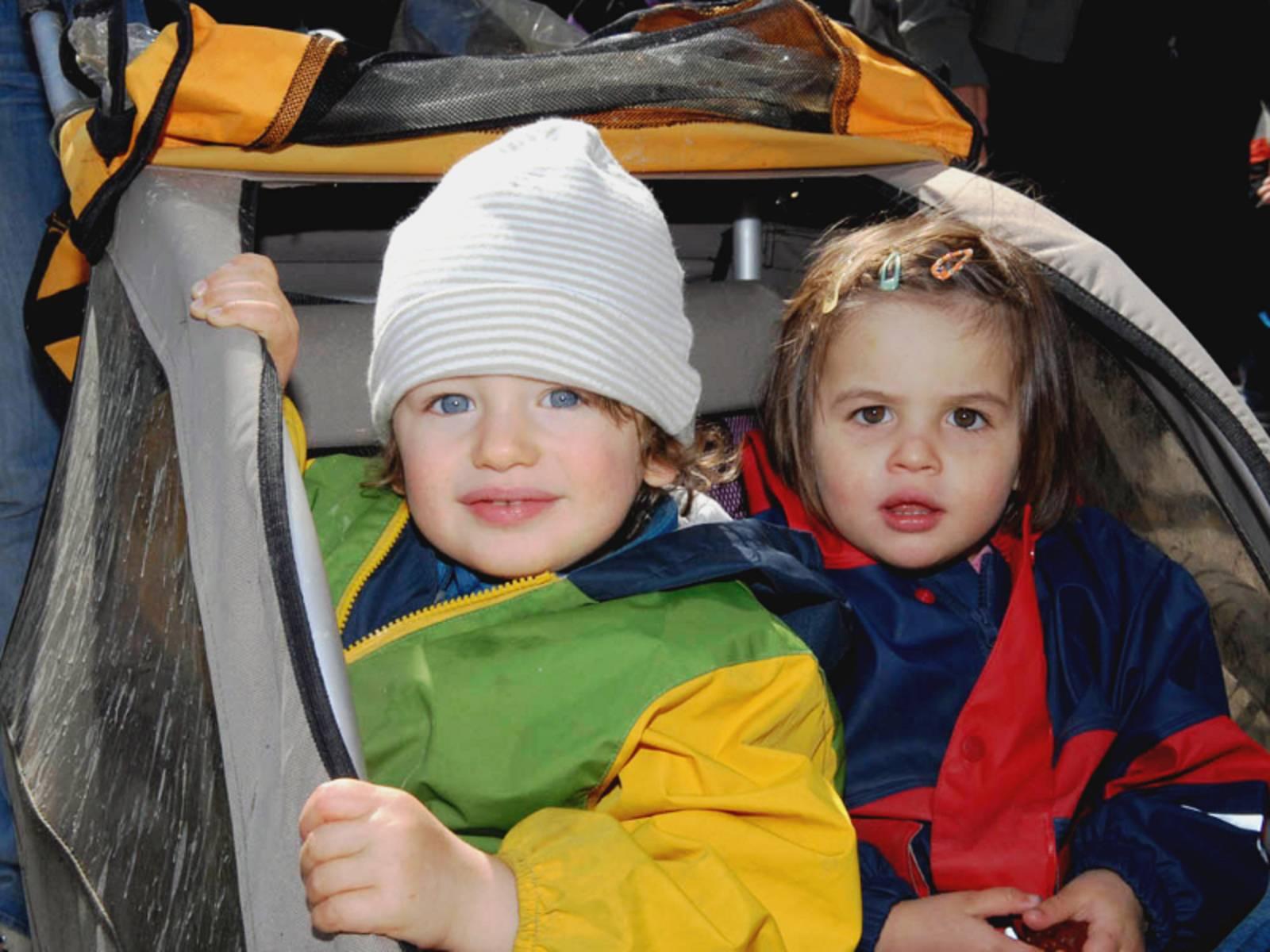 Ein Junge und ein Mädchen sitzen nebeneinander in einem Fahrradanhänger. Bunte Regenkleidung schützt sie vor Wind und Wetter.