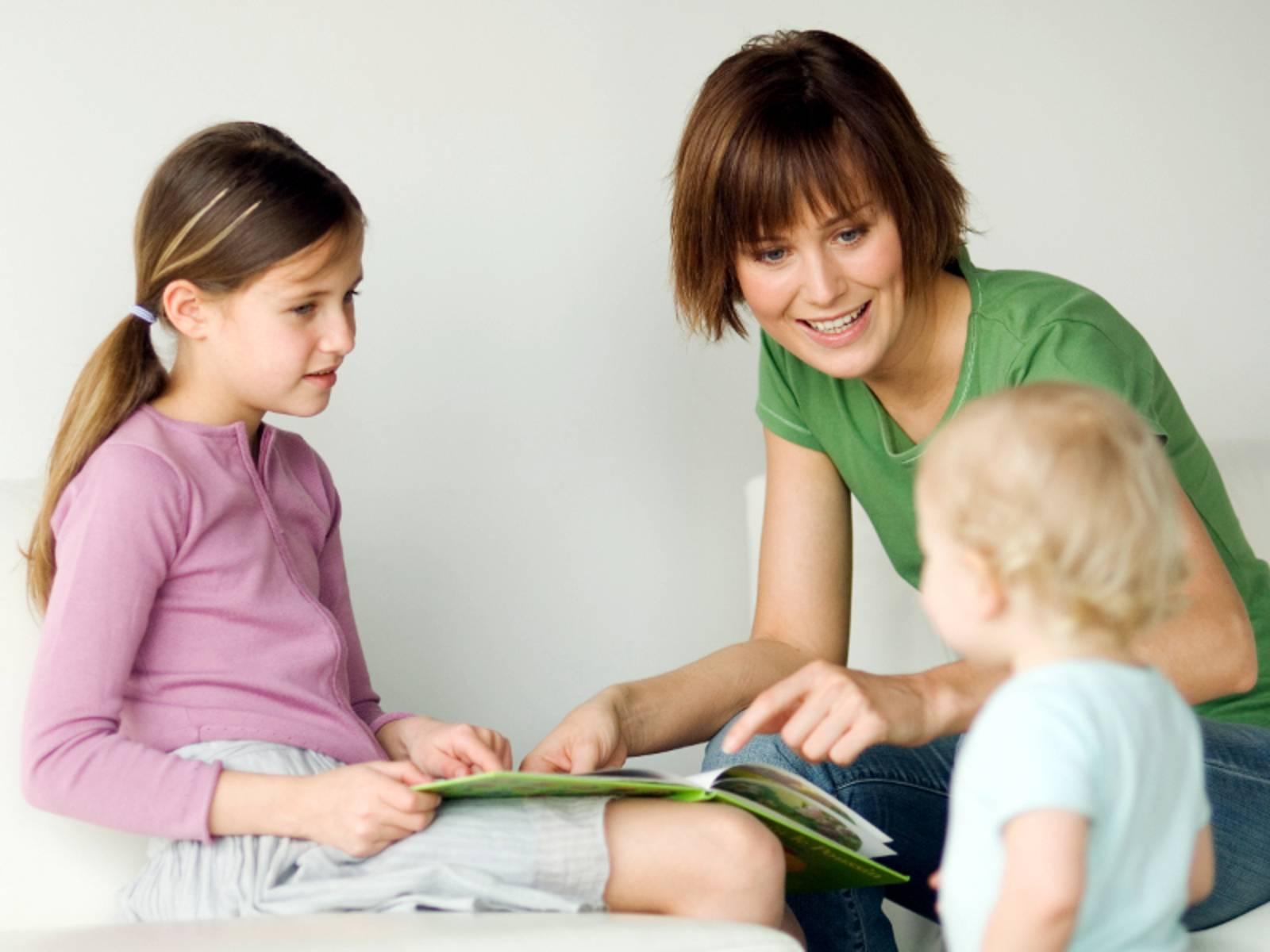 Eine erwachsense Frau schaut sich gemeinsam mit einem Mädchen ein Bilderbuch an, sie sitzen dabei. Ein Kleindkind steht vor den beiden Sitzenden.