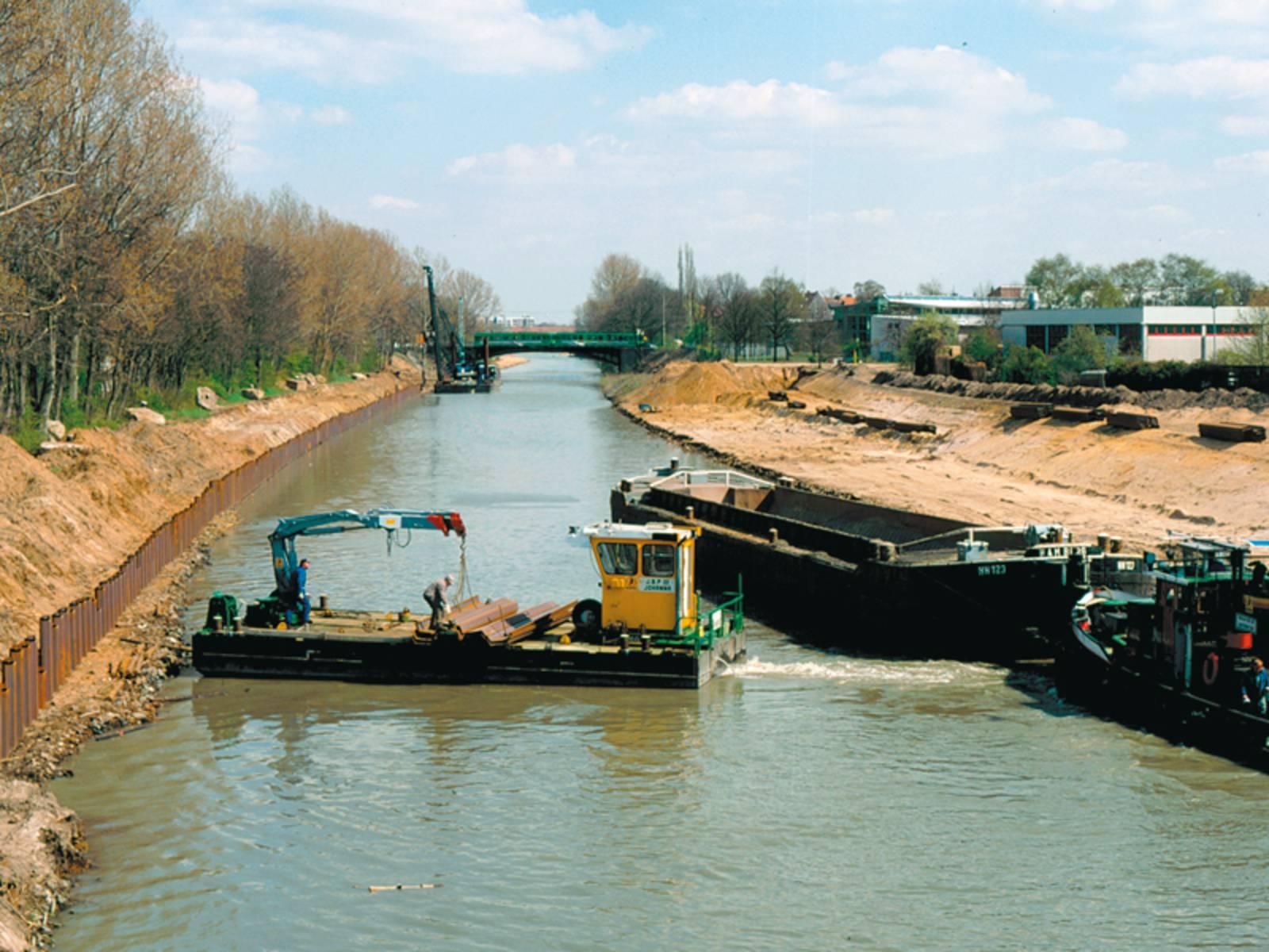 Der Mittellandkanal im Bau, im Vordergrund ein Baggerschiff und ein Lastkan