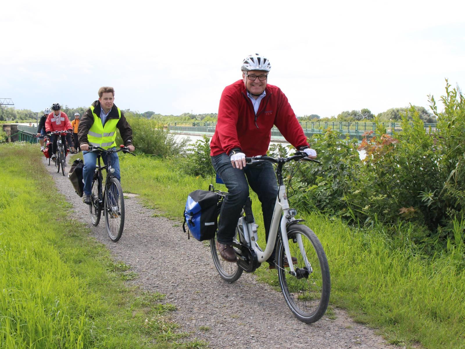 Eine Gruppe von Radfahrern fährt hintereinander auf einem Schotterweg im Grünen, im Hintergrund ist ein Kanal zu sehen.