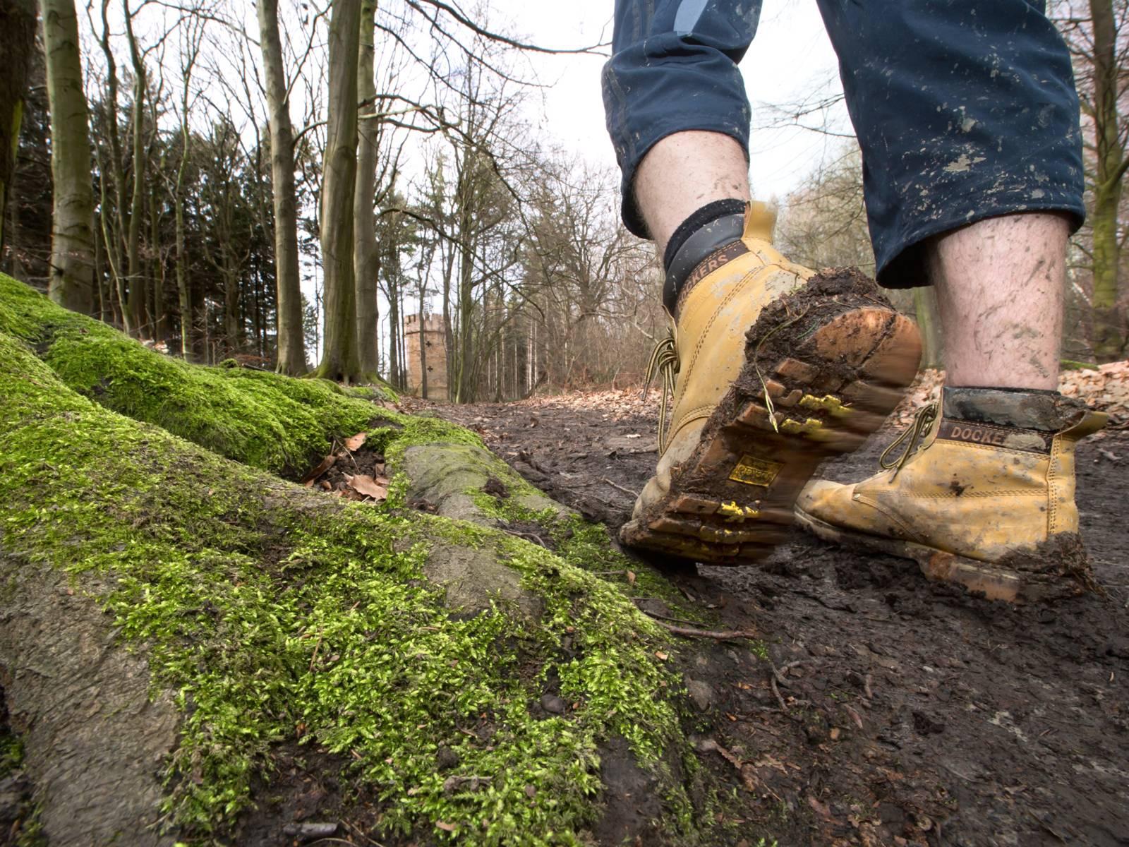 Matschiger Waldweg auf dem jemand mit dreckigen Wanderschuhen geht