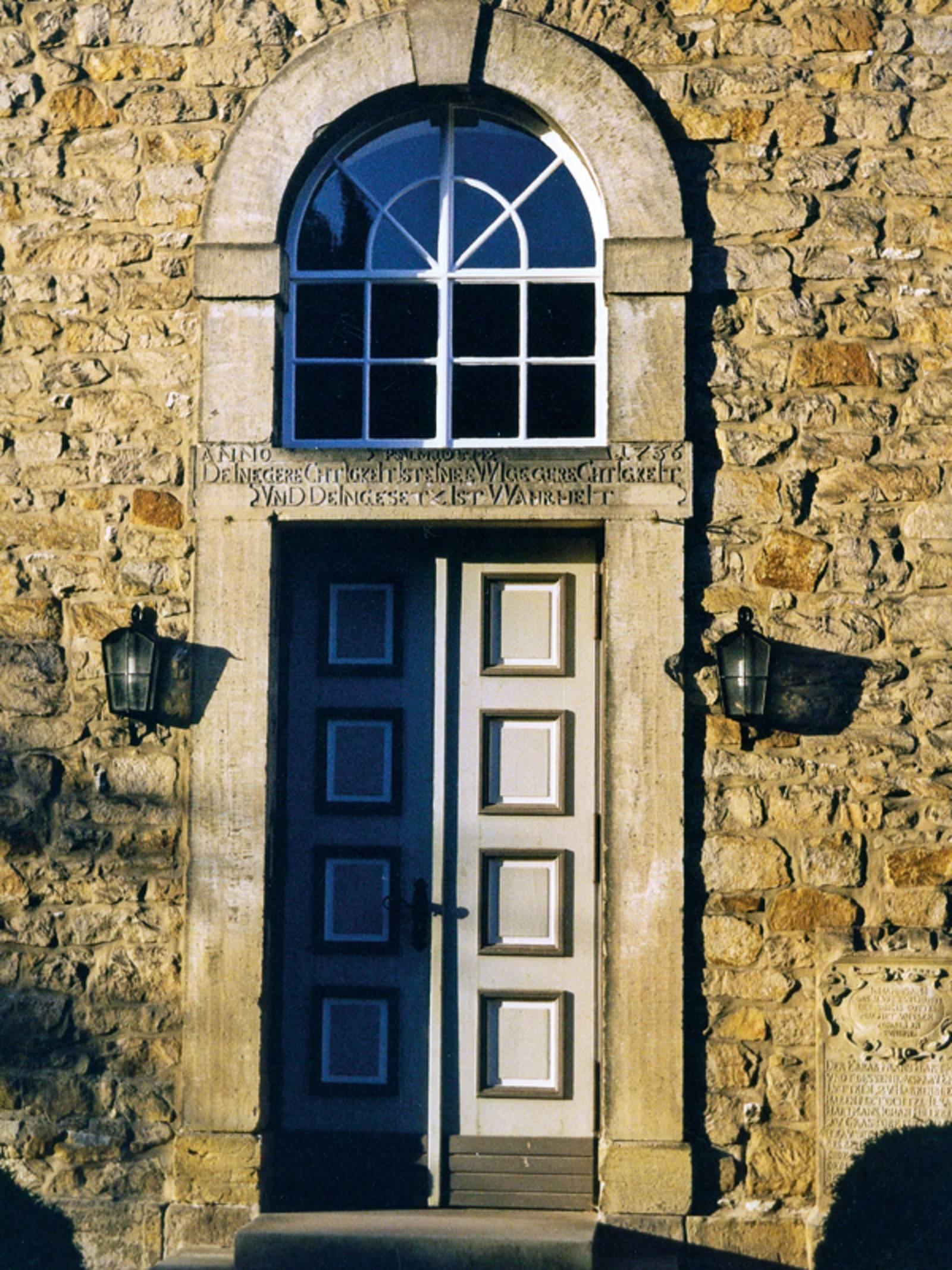 Hohe alte Tür mit einem Rundbogenfenster über dem Türzsturz in einem aus Bruchsteinen gemauerten Gebäude