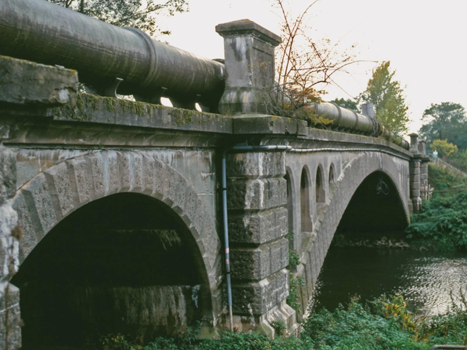 Ältere Brücke aus Stein über die ein sehr dickes Rohr läuft