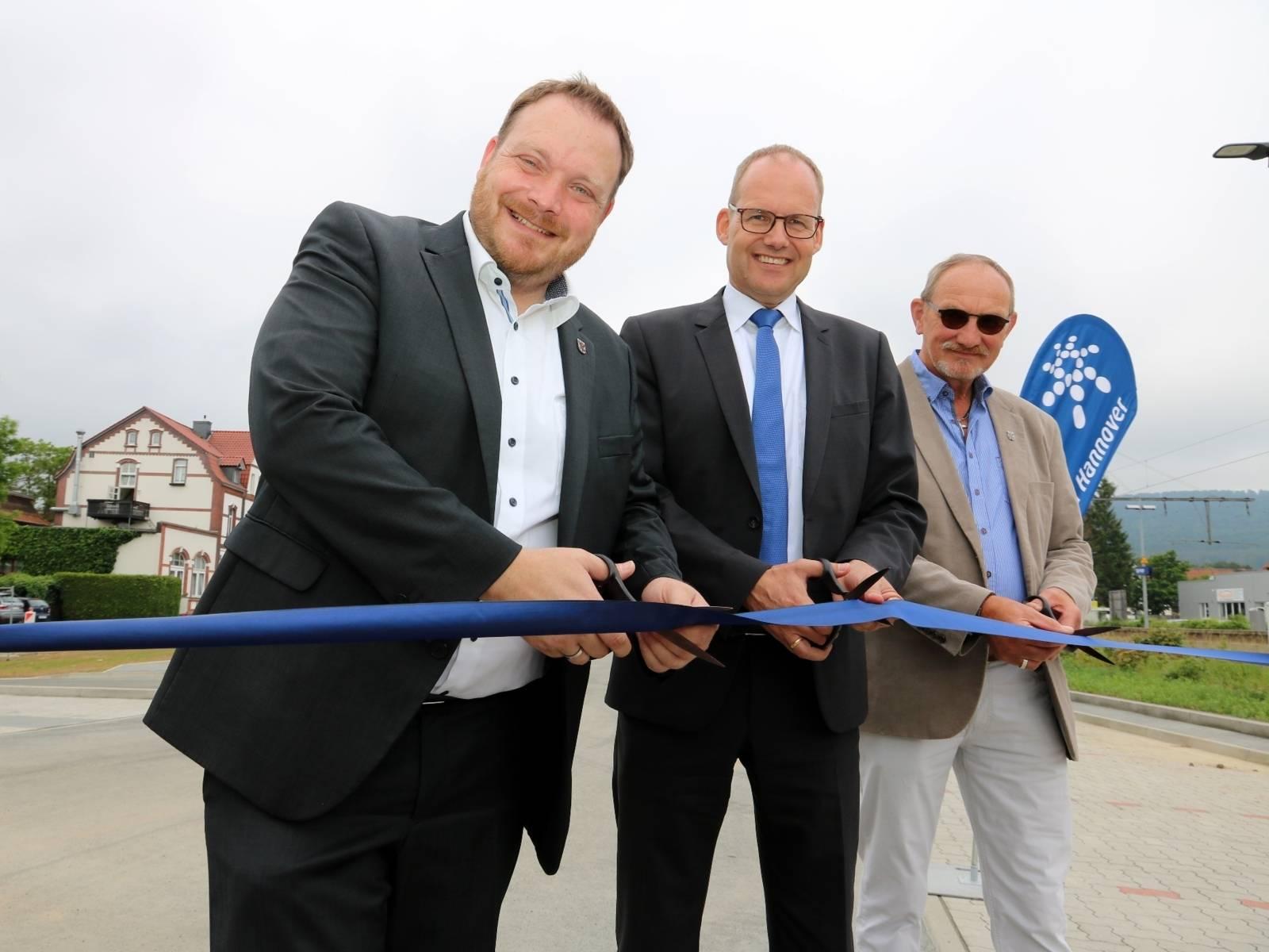Drei Männer stehen im Freien auf einem Parkplatz und durchschneiden ein blaues Band.