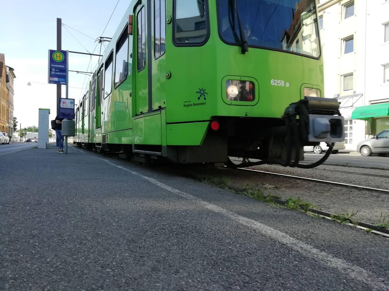 Eine Straßenbahn, die in eine ebenerdige Haltestelle an der Humboldtstraße einfährt. Dahinter ist die Humboldtstraße und ein dreistöckiges Gebäude zu sehen.