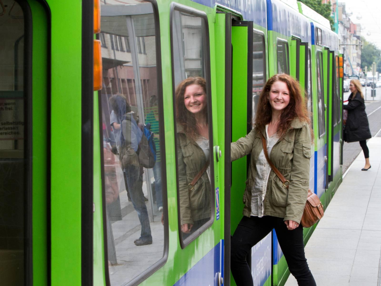 Eine junge Frau steigt in eine Stadtbahn der üstra, ihr Gesicht wird in der Seitenscheibe gespiegelt. Am Fahrzeugkopf steigt eine weitere Person ein.