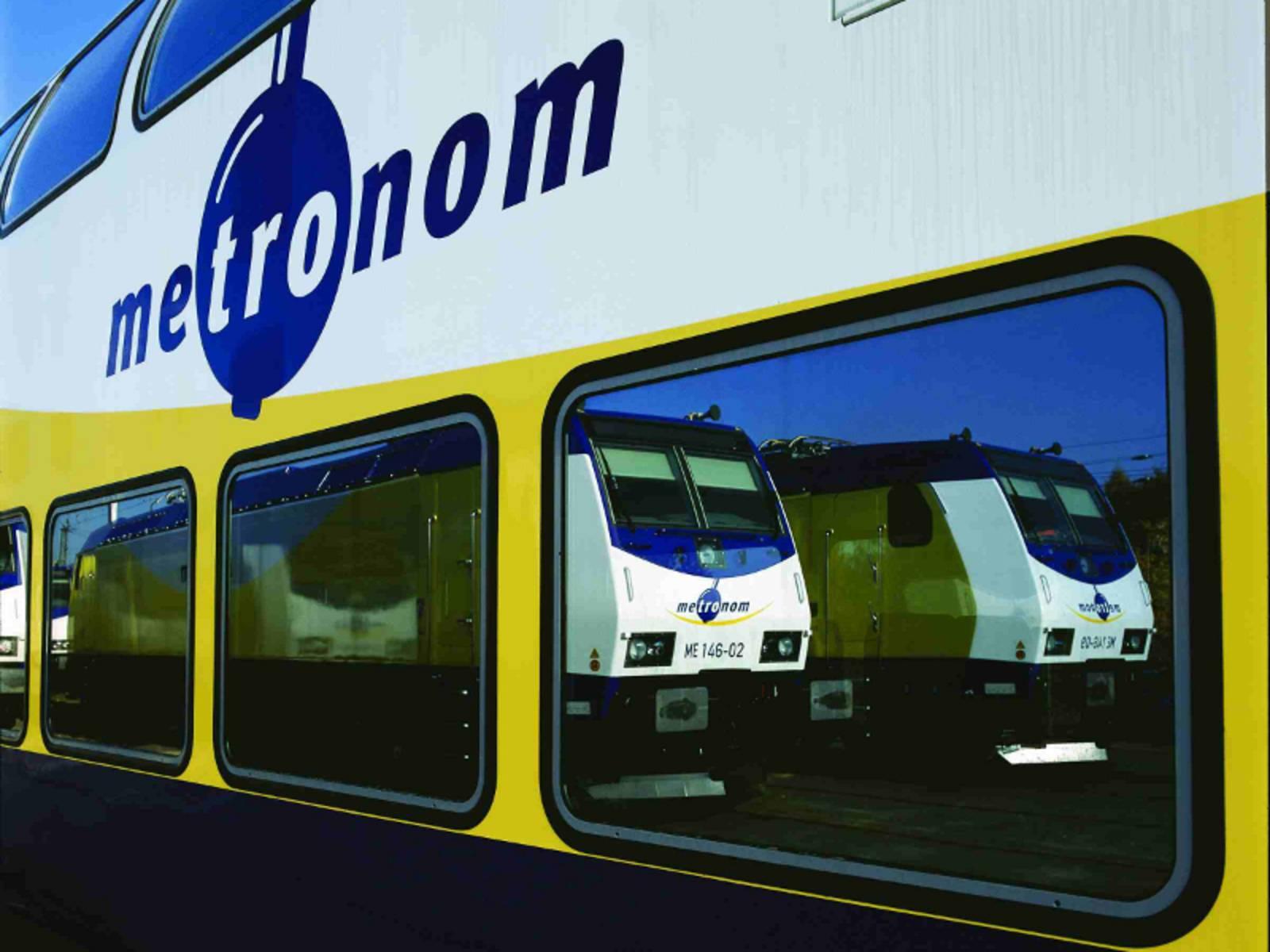 Zug in deren Fenstern sich zwei Triebwagen spiegeln.