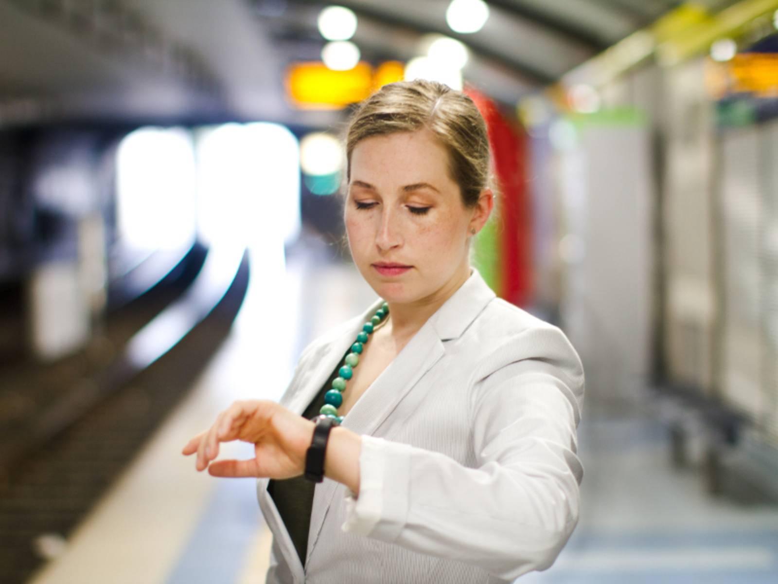 Junge Frau sieht auf ihre Armbanduhr