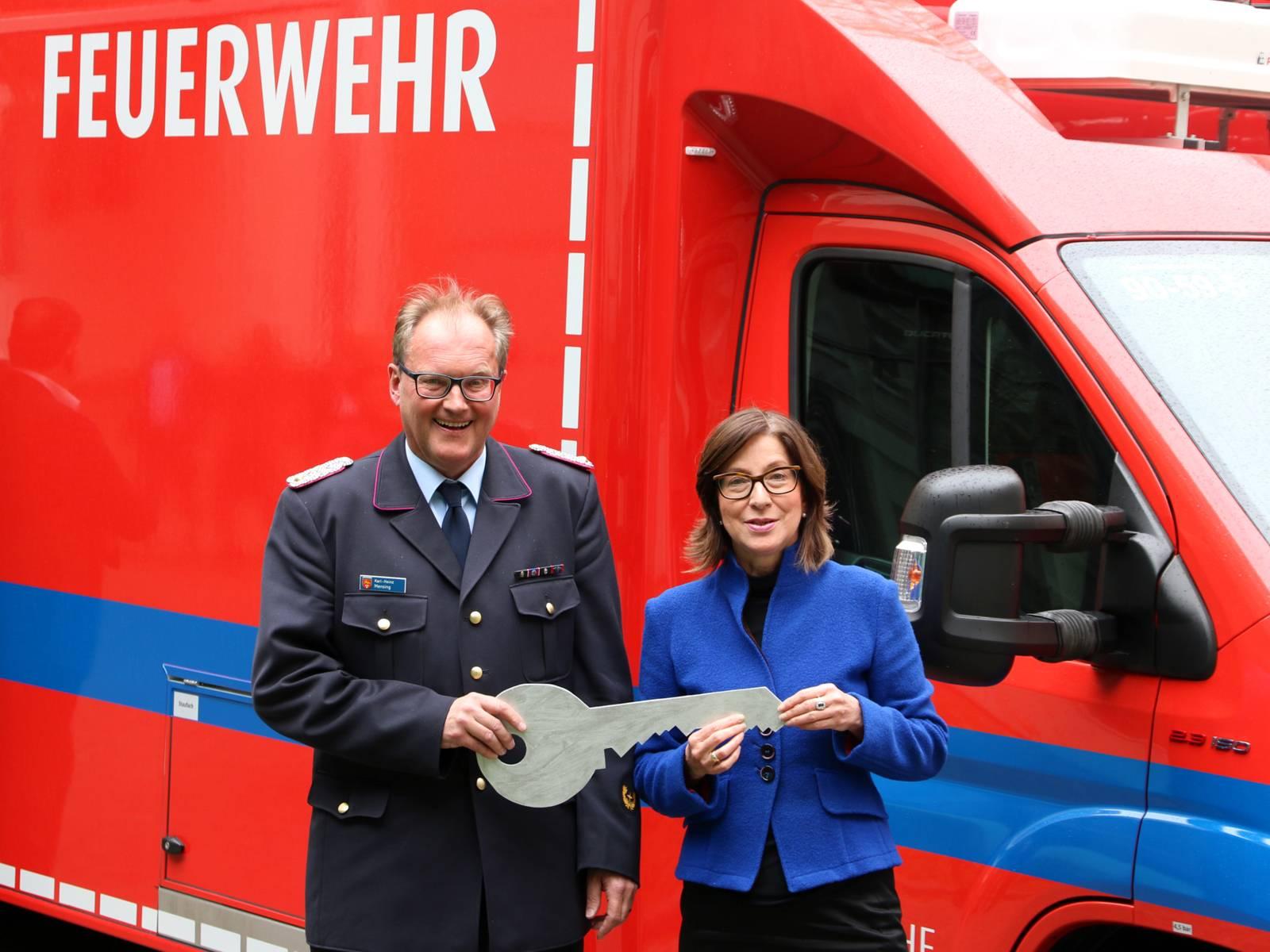 Eine Frau und ein Mann mit einem Schlüssel aus Pappe vor einem Feuerwehrauto.