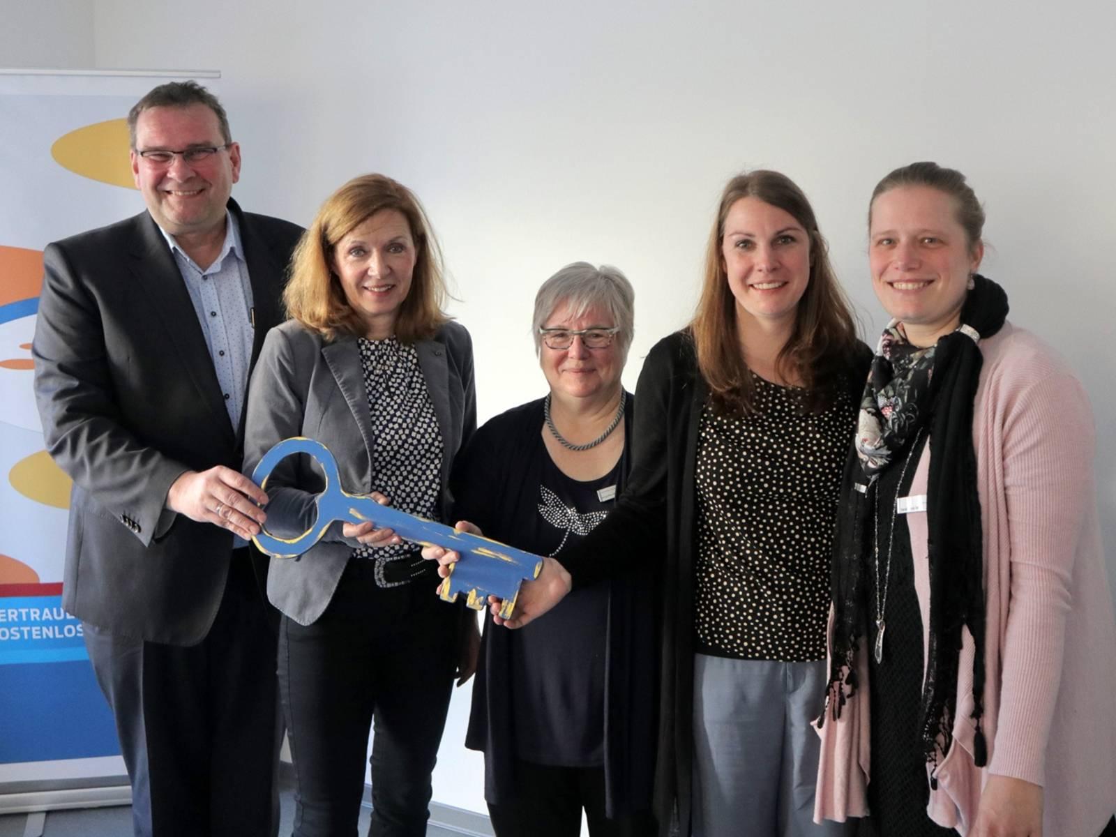 Vier Frauen und ein Mann übergeben einander einen überdimensionalen blauen Schlüssel