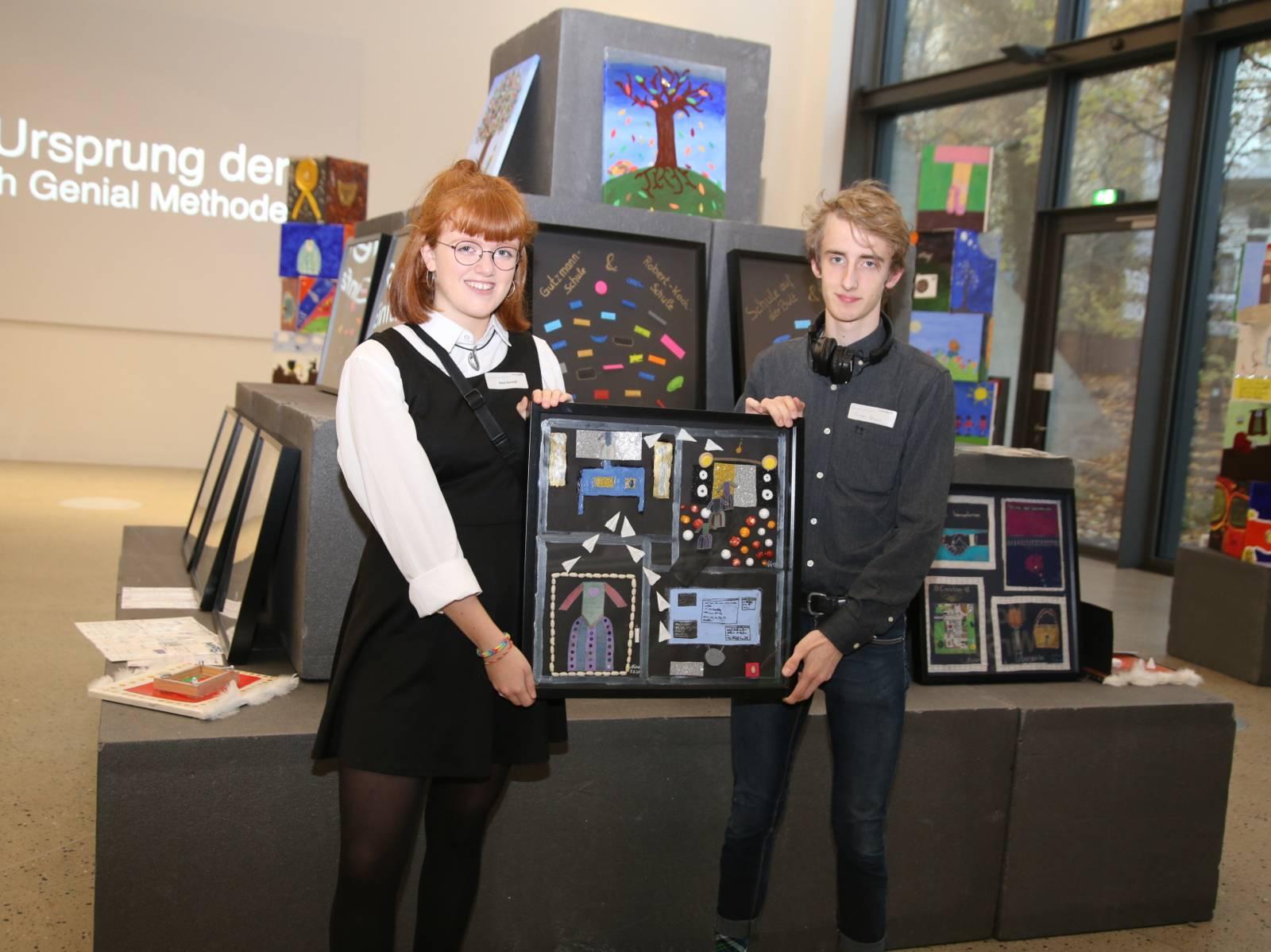 Eine junge Frau und ein junger Mann halten eine Collage in einem Bilderrahmen