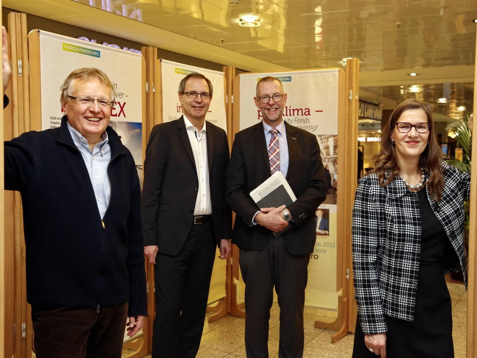 Eine Frau und drei Herren stehen für ein Bild zusammen. Im Hintergrund stehen Stellwände.