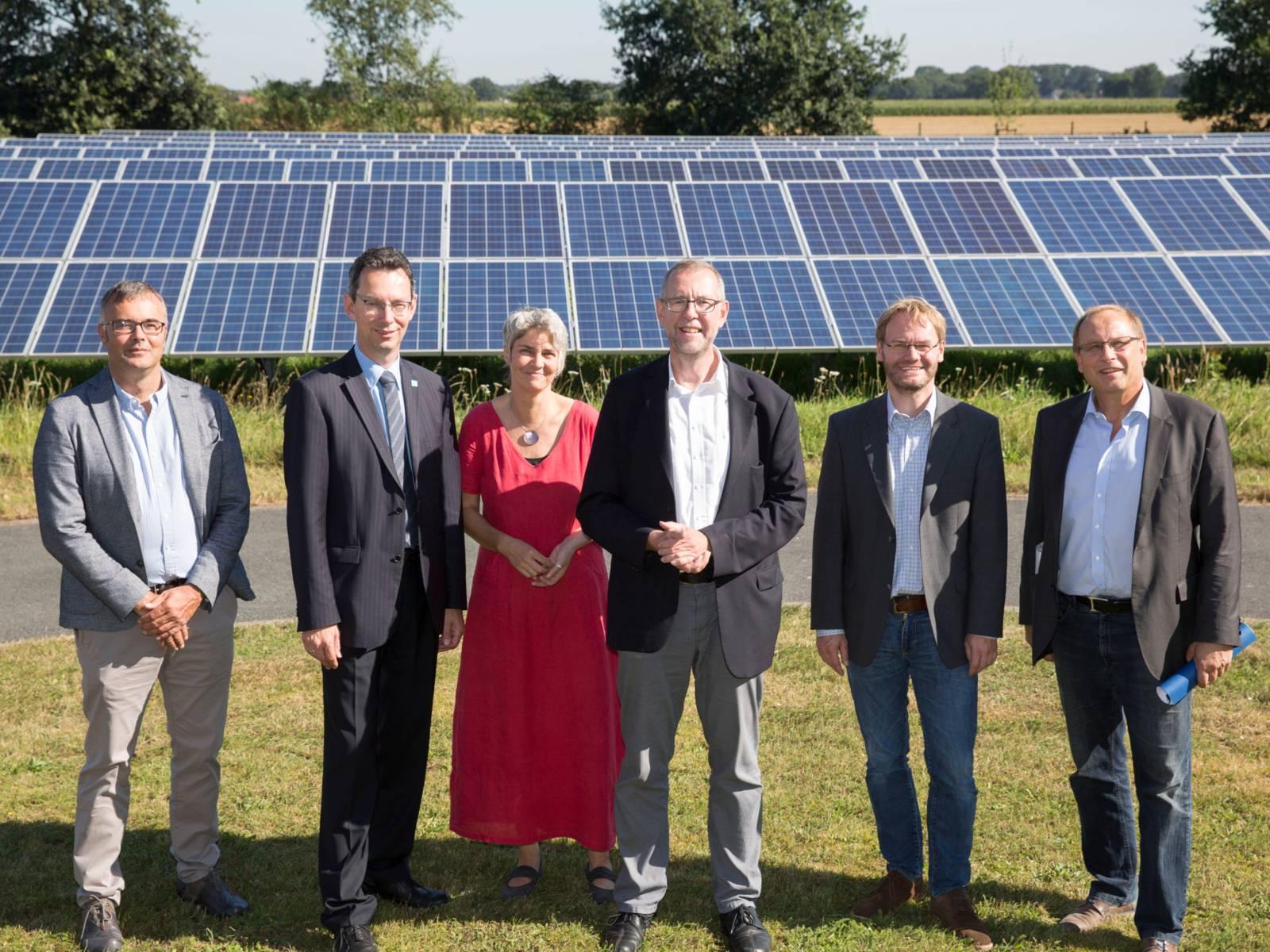 Eine Frau und vier Männer stehen vor einer Solaranlage.