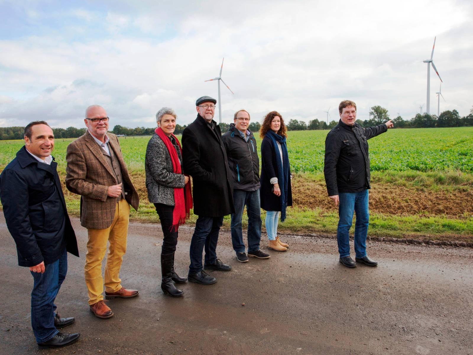 Eine Gruppe steht im ländlichen Bereich auf einem Weg. Im Hintergrund stehen Windkraftanlagen.
